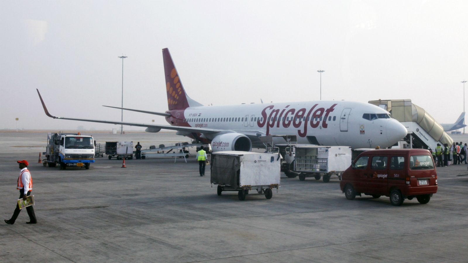 Ground staff work near a SpiceJet Airlines aircraft parked on the tarmac at Bengaluru International Airport in Bangalore March 5, 2012.