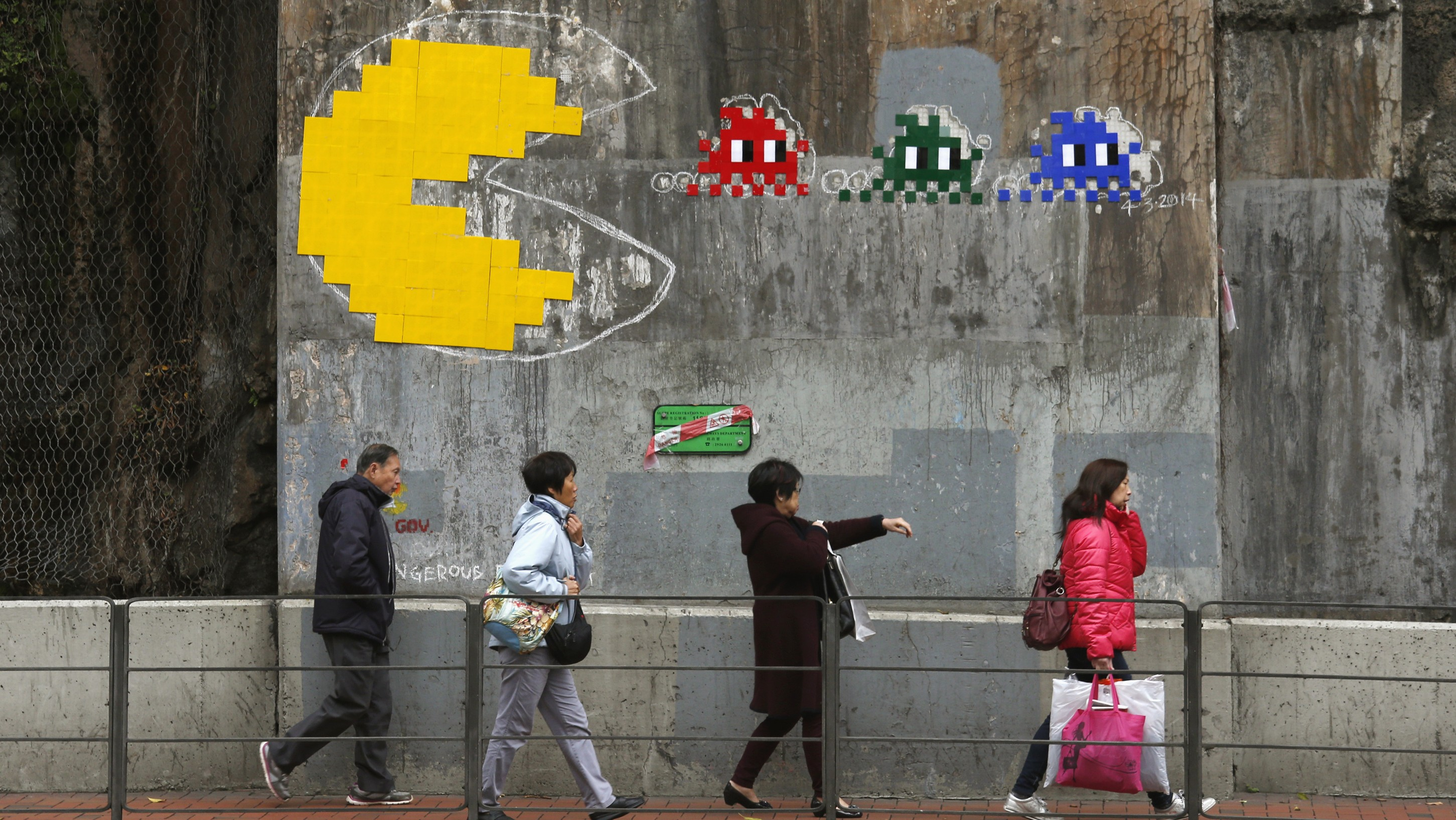 """People walk past a copy of an Pac-Man art piece by French urban artist """"Space Invader"""", in Hong Kong March 7, 2014. The original piece, which was in the same place, was removed by the Hong Kong government for """"safety"""" reasons in February 13, according to local media.   REUTERS/Bobby Yip   (CHINA - Tags: ENTERTAINMENT SOCIETY TPX IMAGES OF THE DAY) - RTR3G5AY"""