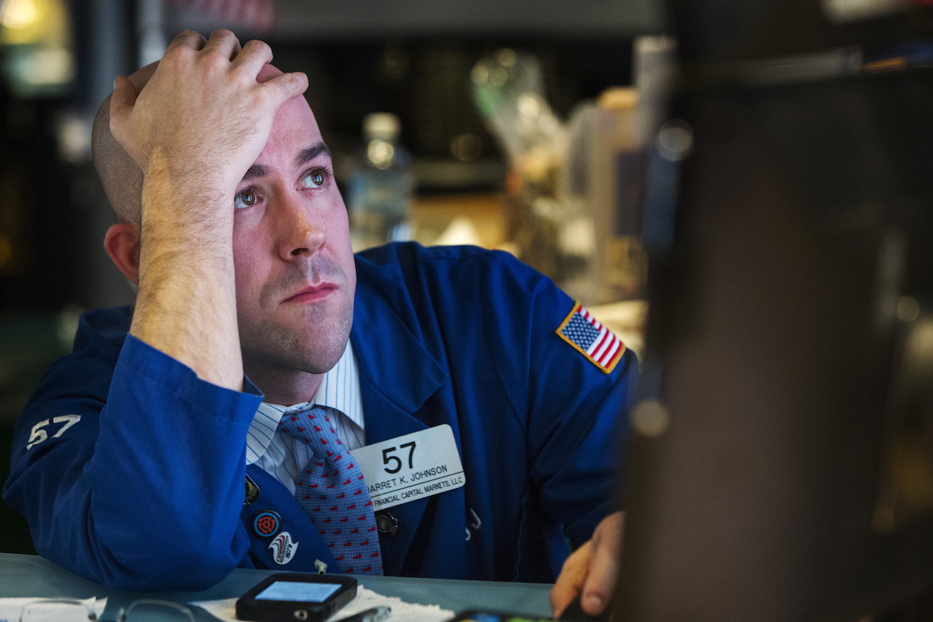 A trader watches the screen at his terminal on the floor of the New York Stock Exchange in New York October 15, 2014. Stocks suffered their biggest losses in years and the dollar slumped on Wednesday after the latest inflation data from the United States and China fanned worries about a global slowdown, driving investors into safe-haven government debt.