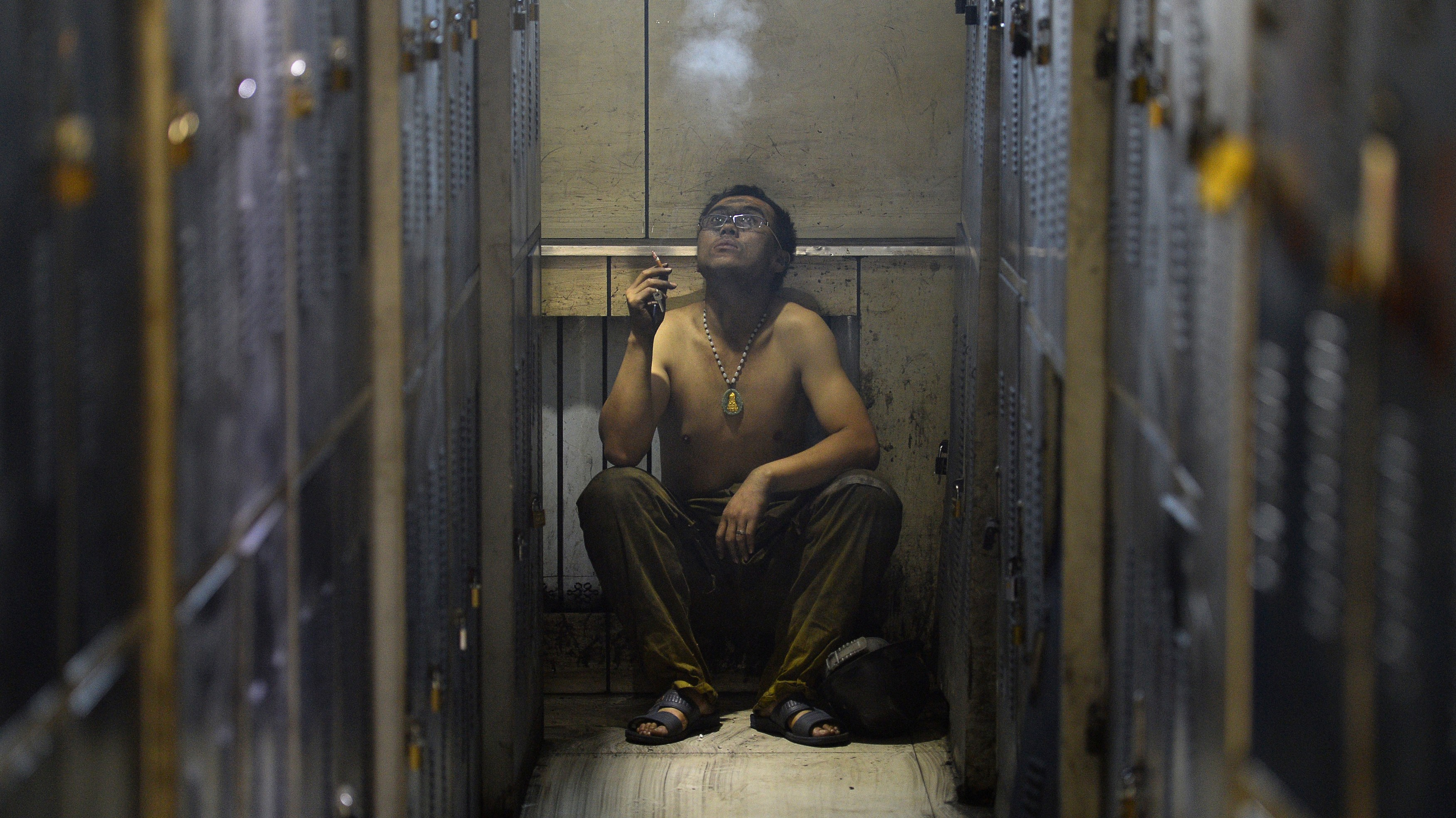 A miner smokes a cigarette next to lockers before showering during a break near a coal mine in Heshun county, Shanxi province December 5, 2014. Chinese coal spot prices are being raised in a domestic market struggling to recover from seven-year lows, desperate for an edge in annual negotiations to supply power plants, key buyers in the world's biggest consumer of coal, industry sources say. REUTERS/Stringer (CHINA - Tags: BUSINESS ENERGY ENVIRONMENT SOCIETY) CHINA OUT. NO COMMERCIAL OR EDITORIAL SALES IN CHINA - RTR4GTCQ