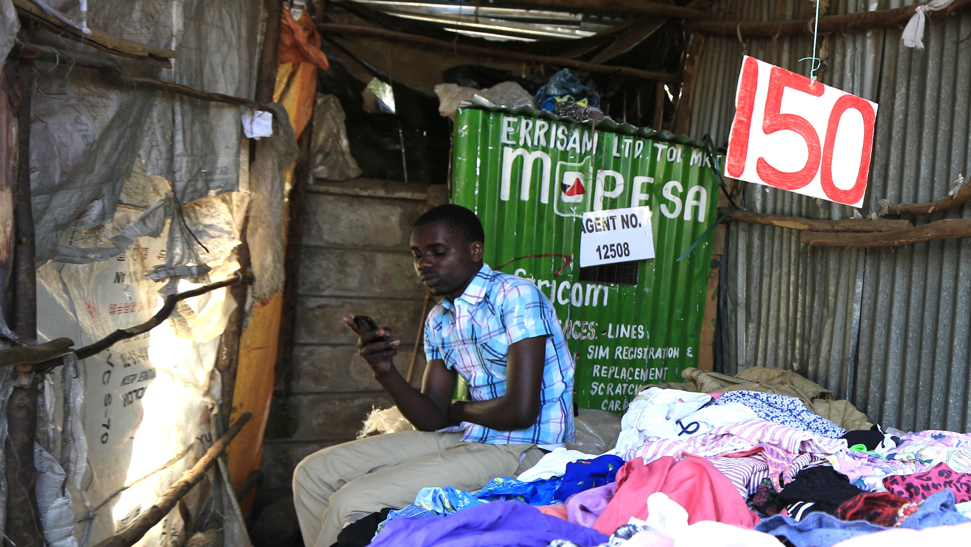 Brian Ochieng waits for M-Pesa customers at his second hand clothing shop in Kibera in Kenya's capital Nairobi December 31, 2014. Safaricom, Kenya's biggest telecoms firm, is a model of how technology can be used to financially include millions of people with mobile telephones but without access to traditional infrastructure such as the banks that are available to the wealthy or those living in cities. Safaricom in 2007 pioneered its M-Pesa mobile money transfer technology, now used across Africa, Asia and Europe. It proved that money can be made from people who earn a few dollars a day. REUTERS/Noor Khamis (KENYA - Tags: BUSINESS SOCIETY SCIENCE TECHNOLOGY TELECOMS) - RTR4JQ0Y