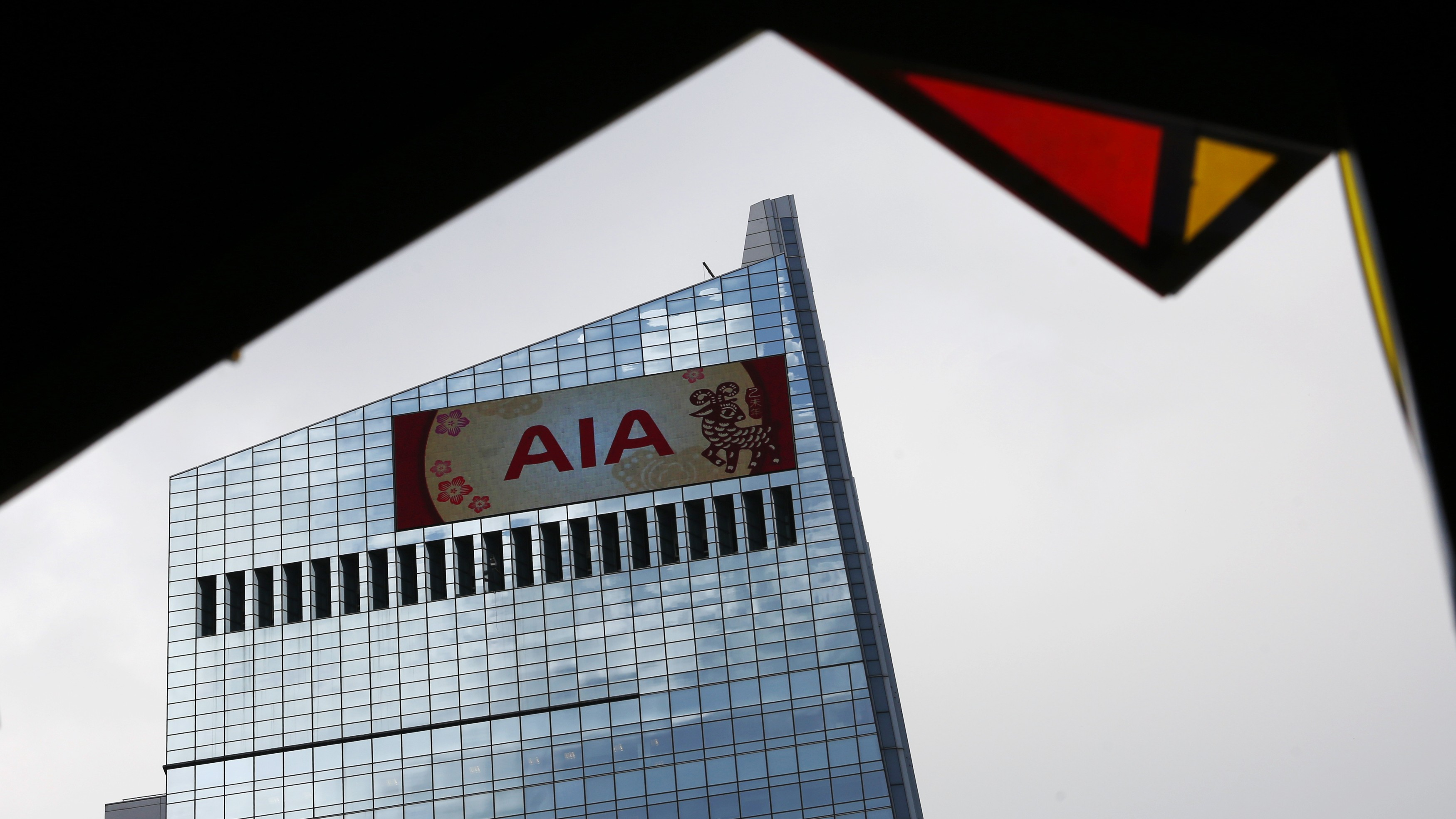 The company logo of AIA and Chinese New Year illustrations are seen on a panel on the AIA Central building in Hong Kong February 26, 2015. AIA Group Ltd, Asia's third-largest life insurer by market capitalisation, reported a record 24 percent annual rise in the value of new business as it reaped the rewards of an expanded China salesforce and strong growth in Hong Kong.     REUTERS/Bobby Yip  (CHINA - Tags: BUSINESS LOGO) - RTR4R809