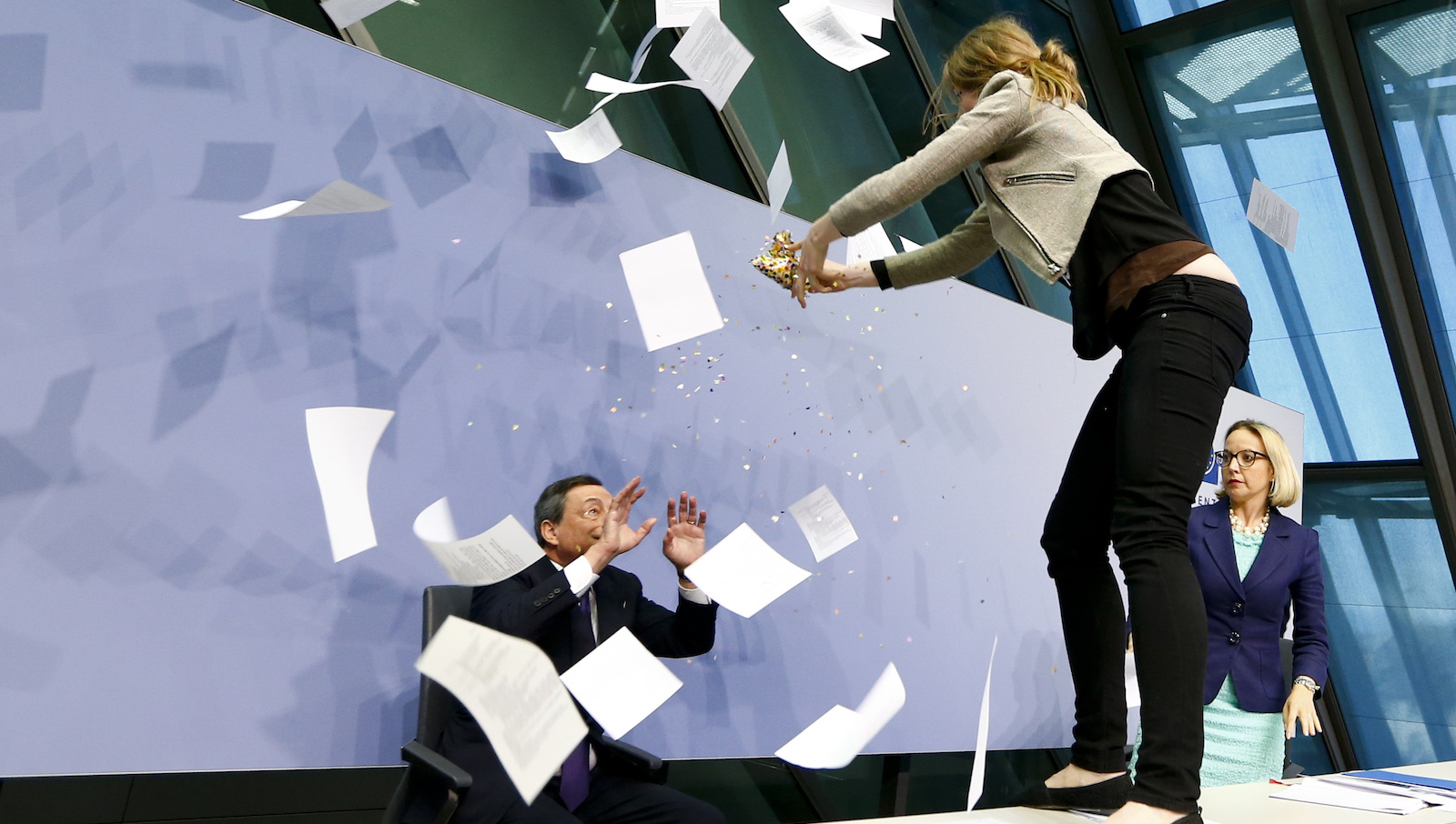 A protester jumps on the table in front of the European Central Bank President Mario Draghi during a news conference in Frankfurt, April 15, 2015. The news conference was disrupted on Wednesday when a woman in a black T-shirt jumped on the podium.   REUTERS/Ralph Orlowski  TPX IMAGES OF THE DAY - RTR4XFTD