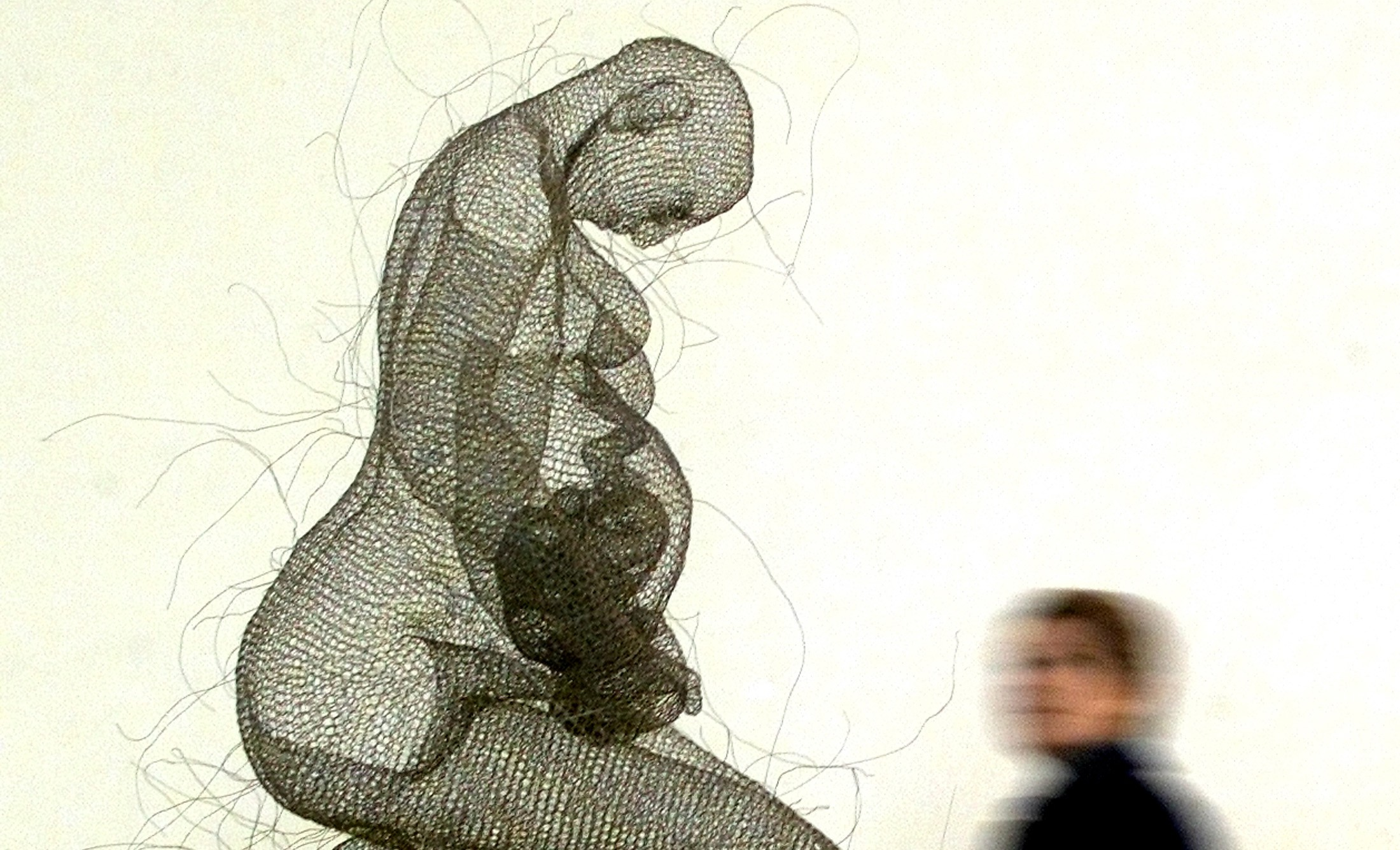 "A visitor looks at a sculpture of a pregnant woman by artist Nadya Zubareva made of wire and installed in the Museum of Anna Akhmatova in St.Petersburg, October 28, 2003. Artists from Russia and the U.S. present modern art in an exhibition called ""Touch me"". REUTERS/Alexander Demianchuk  AD/CVI - RTR5QIG"