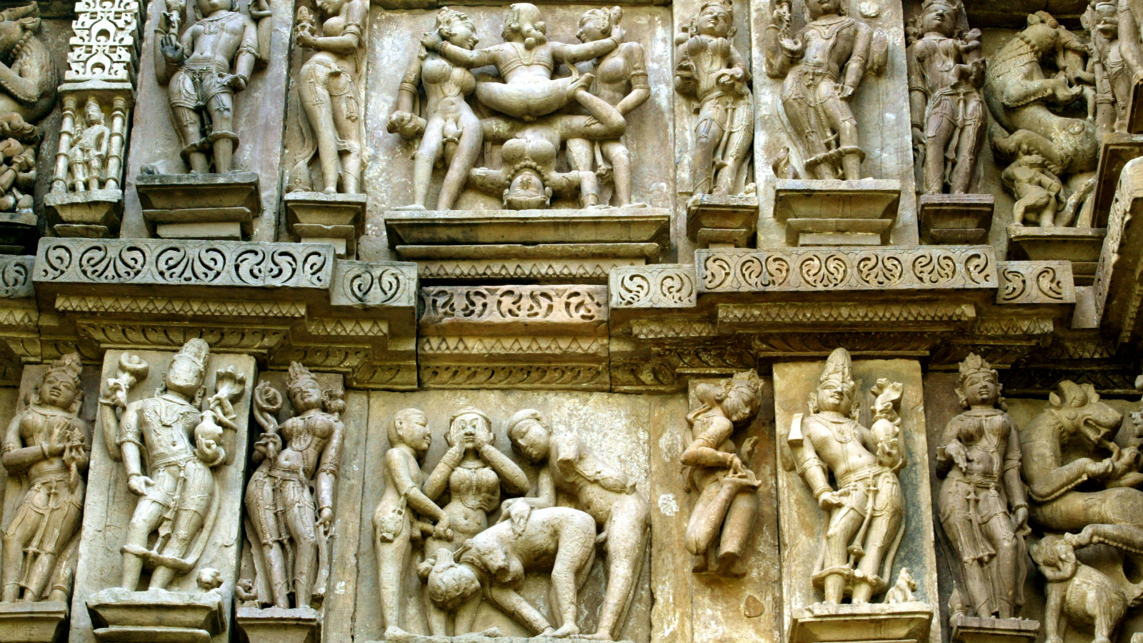 Erotic Hindu sculptures on the outer walls of a temple in the Indian town of Khajuraho in the central Indian state of Madhya Pradesh November 18, 2003. Temples in Khajuraho are famous for displaying erotic carvings and sculptures that date back to hundreds of years in a country that gave birth to the Kama Sutra.