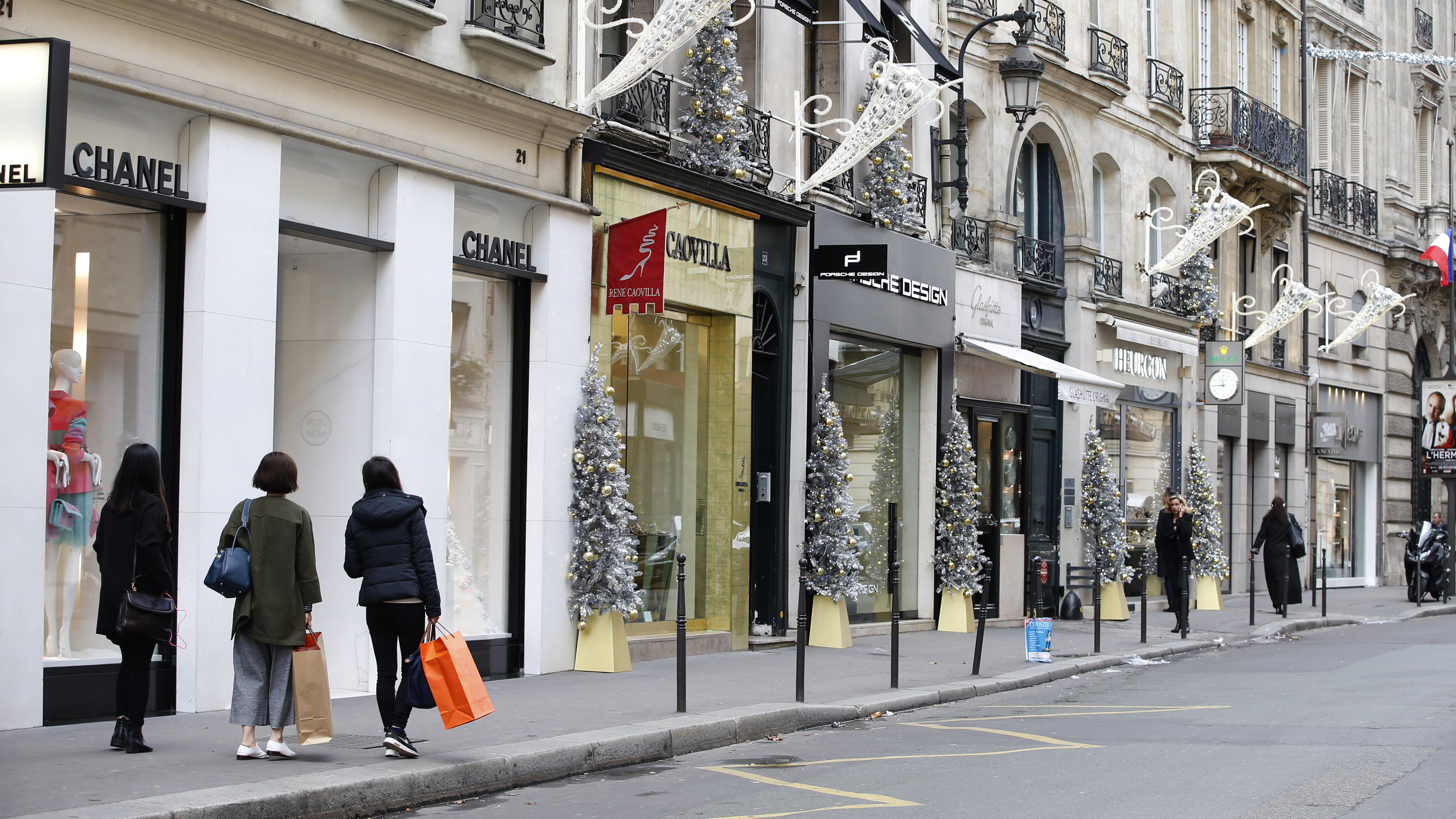 Customers stand on an uncrowded sidewalk in front of shops selling luxury goods Rue du Faubourg Saint-Honore in Paris after last Friday's series of deadly attacks in the French capital, France, November 18, 2015.