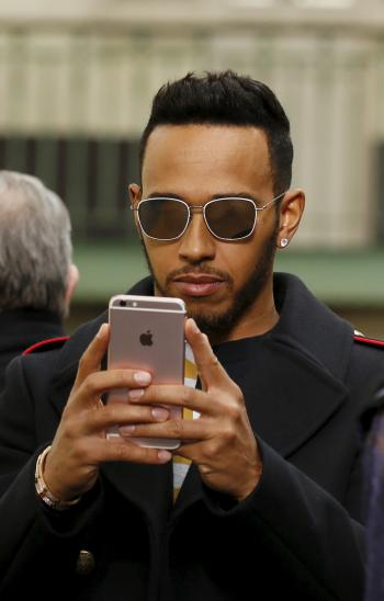 Formula One driver Lewis Hamilton takes a picture with his mobile phone as he attends designer Bill Gaytten's Fall/Winter 2016/2017 women's ready-to-wear collection for fashion house John Galliano in Paris, France, March 6, 2016.