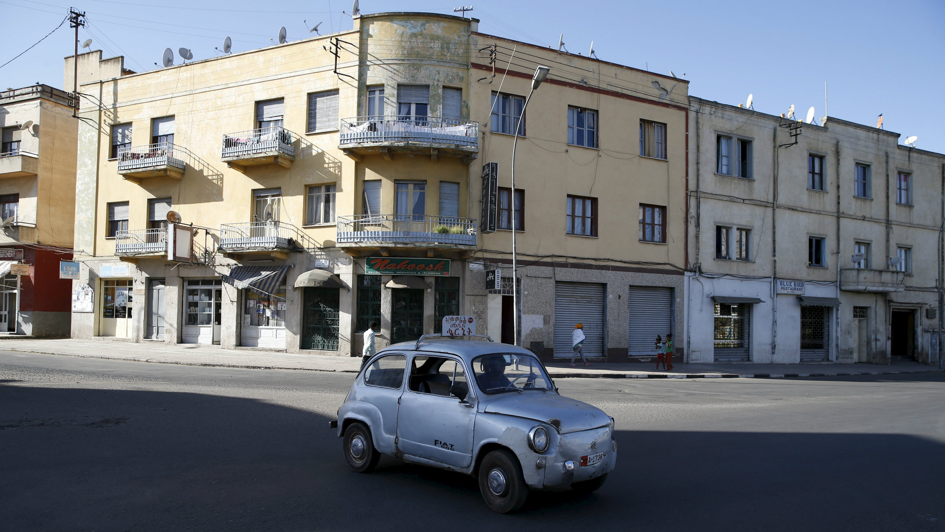"""A Fiat car drives along a street in Eritrea's capital Asmara, February 20, 2016. Eritrea's capital city boasts one of the world's finest collections of early 20th century architecture, which the authorities want declared a UNESCO World Heritage Site. When Italy's colonial experiment in Eritrea ended in 1941, it left behind an array of Rationalist, Futurist, Art Deco and other styles of Modernism in Asmara, a city they nicknamed """"La Piccola Roma"""" or """"Little Rome""""."""