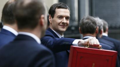 Britain's Chancellor of the Exchequer Osborne holds up his budget case for the cameras as he stands outside...