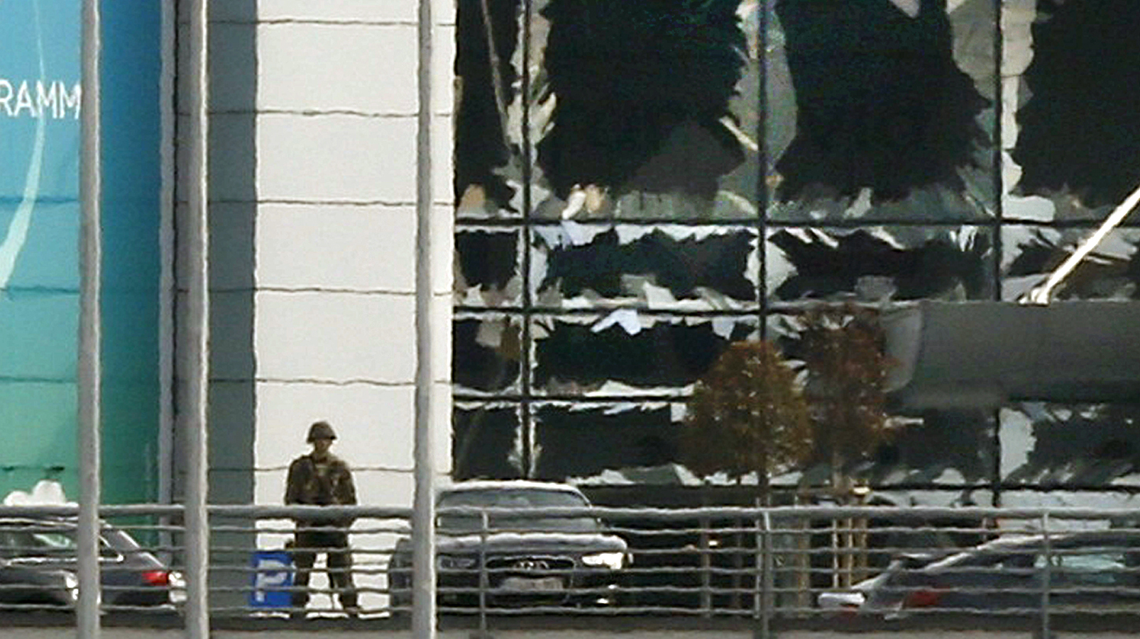 A soldier stands near broken windows after explosions at Zaventem airport near Brussels, Belgium