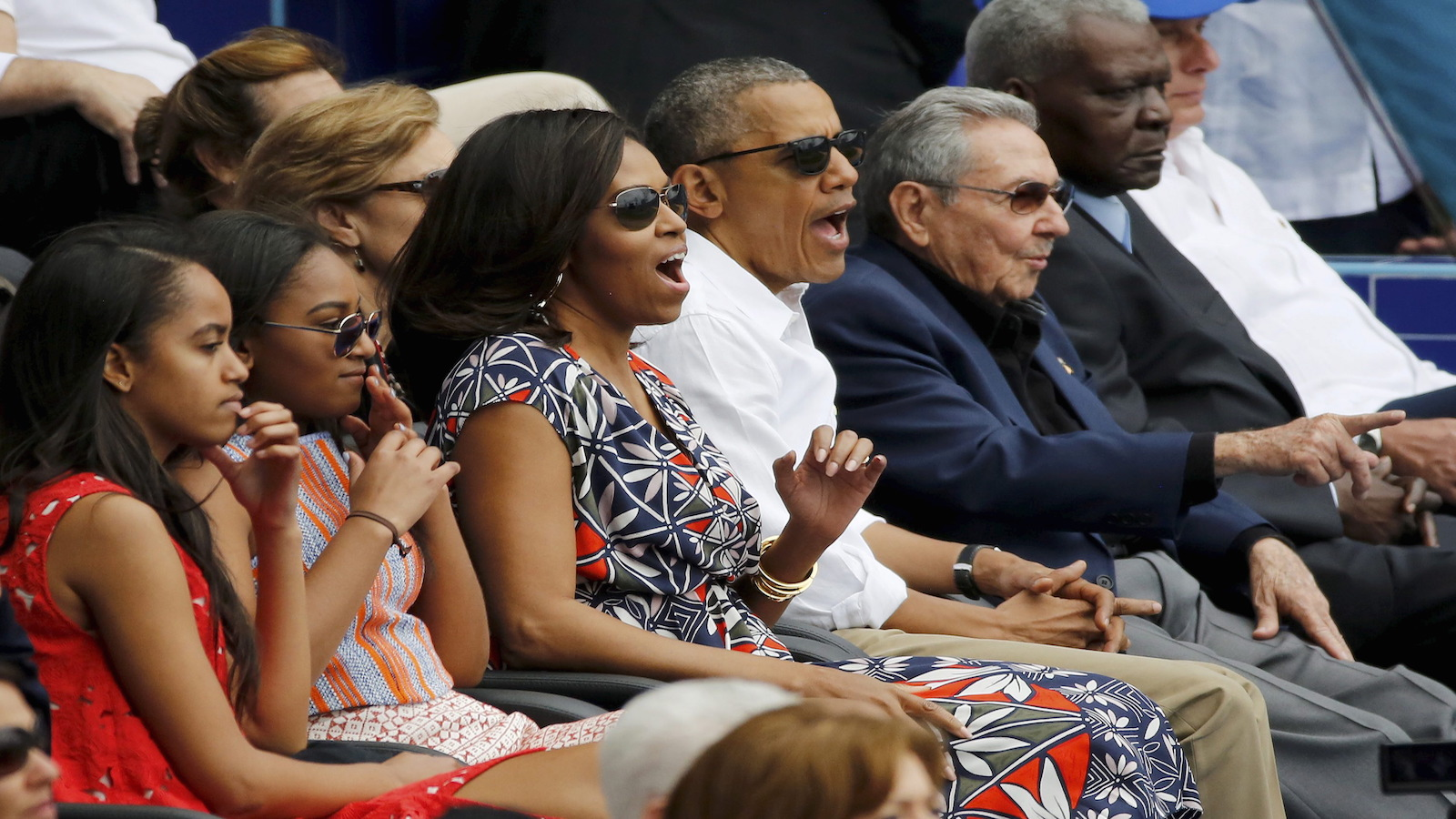 U.S. President Barack Obama and his family react along with Cuban President Raul Castro to an exhibition baseball game between the Cuban National team and the MLB Tampa Bay Rays at Estadio Latinoamericano in Havana March 22, 2016.