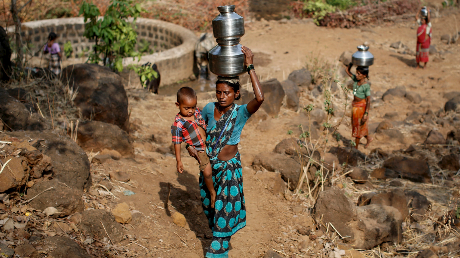 "DATE IMPORTED:June 04, 2015Shivarti, the second wife of Namdeo, holds her grandson while carrying metal pitchers filled with water from a well outside Denganmal village, Maharashtra, India, April 21, 2015. In Denganmal, a village in Maharashtra state, some men take a second or third wife just to make sure their households have enough drinking water. Becoming what are known as ""water wives"" allows the women, often widows or single mothers, to regain respect in conservative rural India by carrying water from the well quite some distance from the remote village. When the water wife, who does not usually share the marital bed, becomes too old to continue, the husband sometimes takes a third and younger spouse to fetch the water in metal pitchers or makeshift containers. REUTERS/Danish Siddiqui"