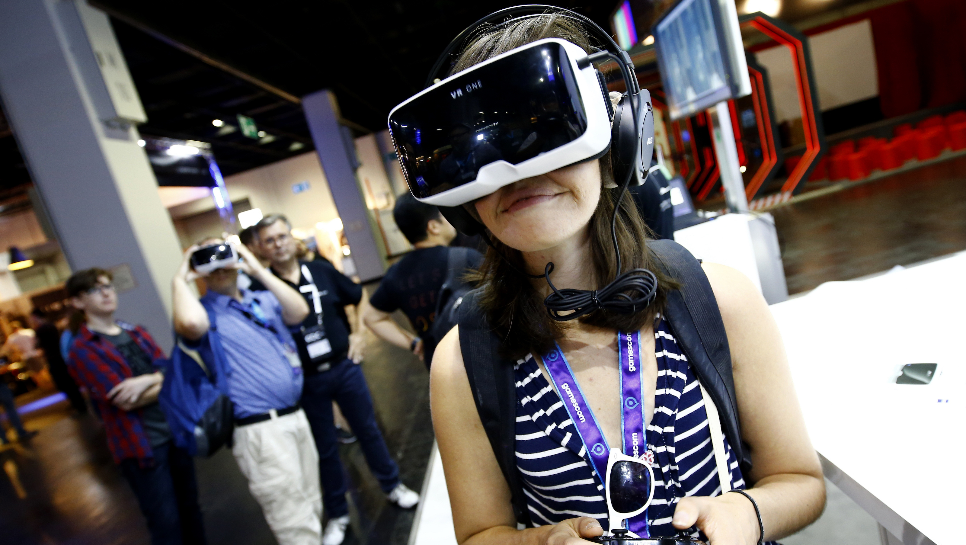 """A woman tests a virtual reality headset """"VR One"""" developed by a German manufacturer Zeiss at the Gamescom 2015 fair in Cologne, Germany August 5, 2015. The Gamescom convention, Europe's largest video games trade fair, runs from August 5 to August 9. REUTERS/Kai Pfaffenbach  - RTX1N431"""
