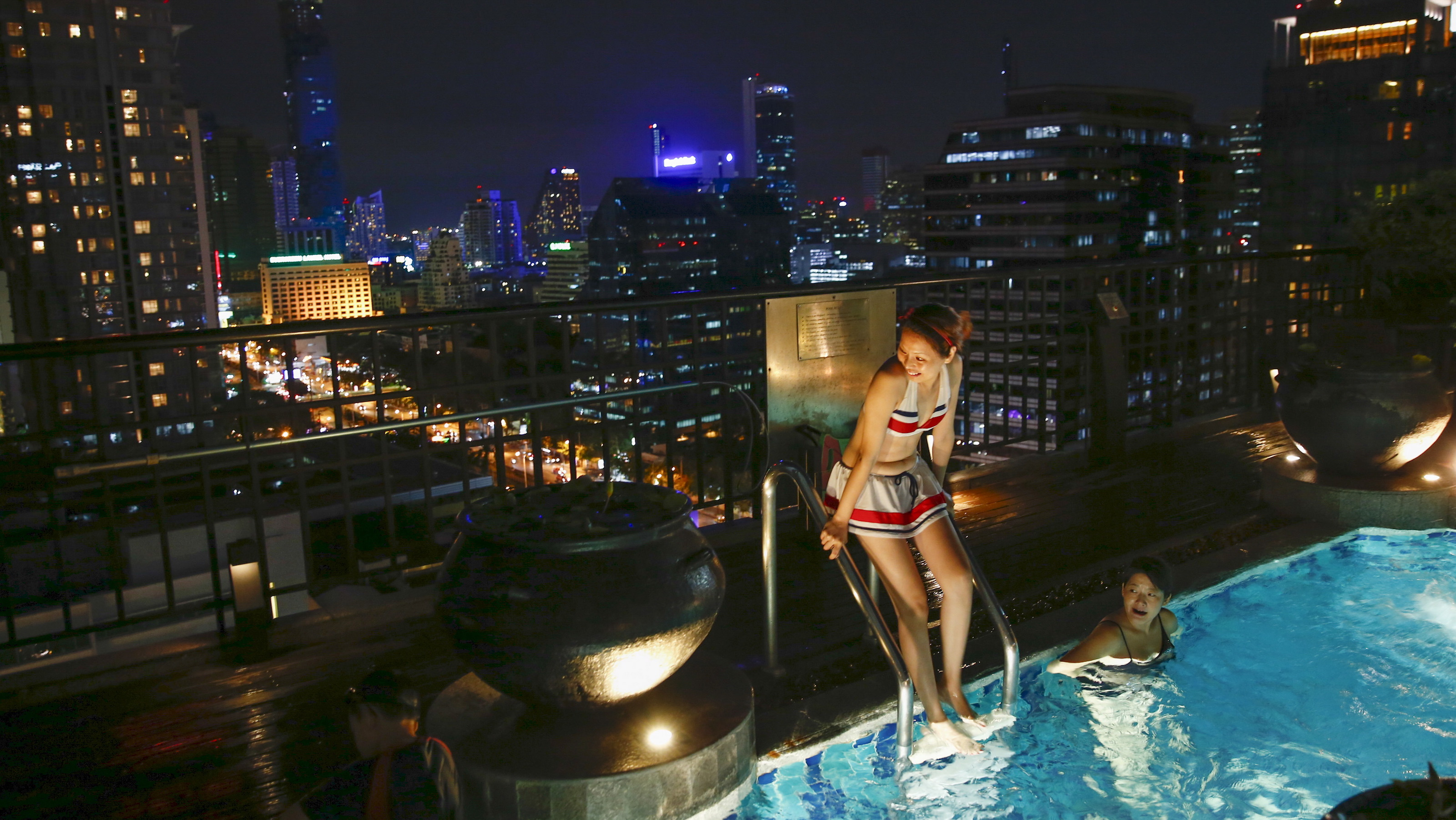Chinese tourists swim in a roof-top swimming pool in a hotel in Bangkok, Thailand September 9, 2015.    REUTERS/Jorge Silva - RTX1TR2I