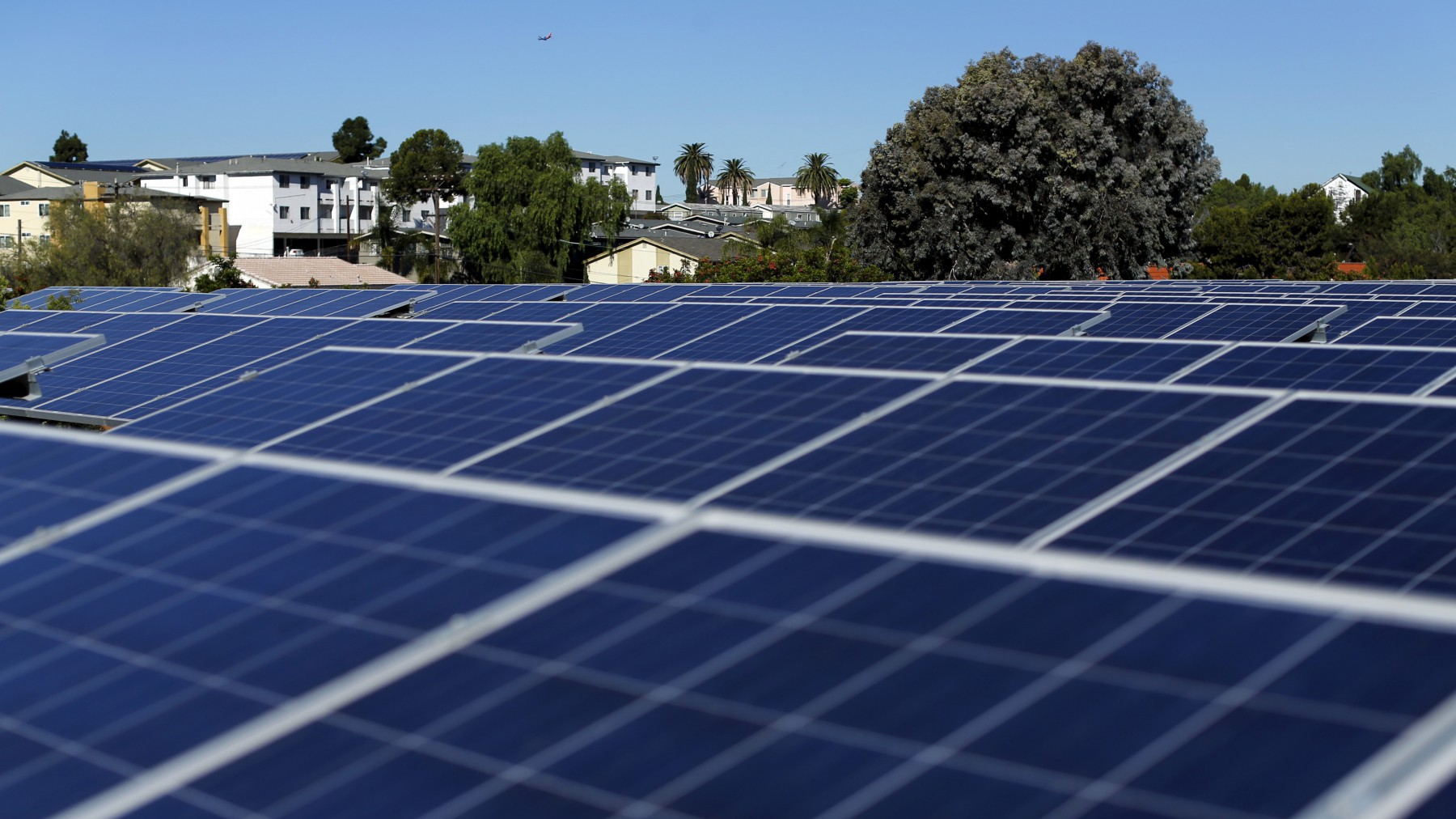 Solar panels are shown on top of a Multifamily Affordable Solar Housing-funded (MASH) housing complex in National City, California..
