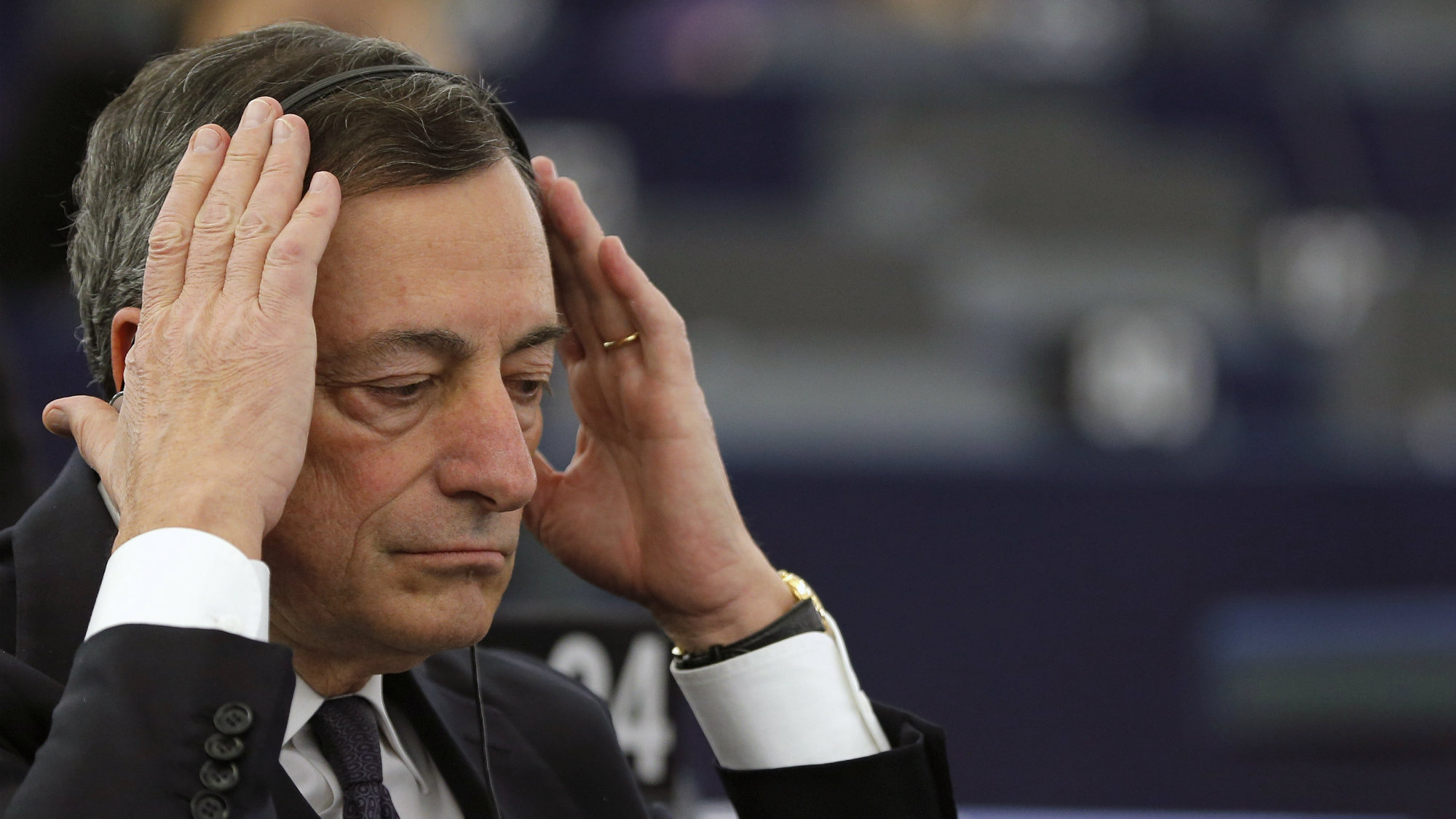 European Central Bank President Mario Draghi adjusts his earphones as he attends a debate on the ECB Annual Report