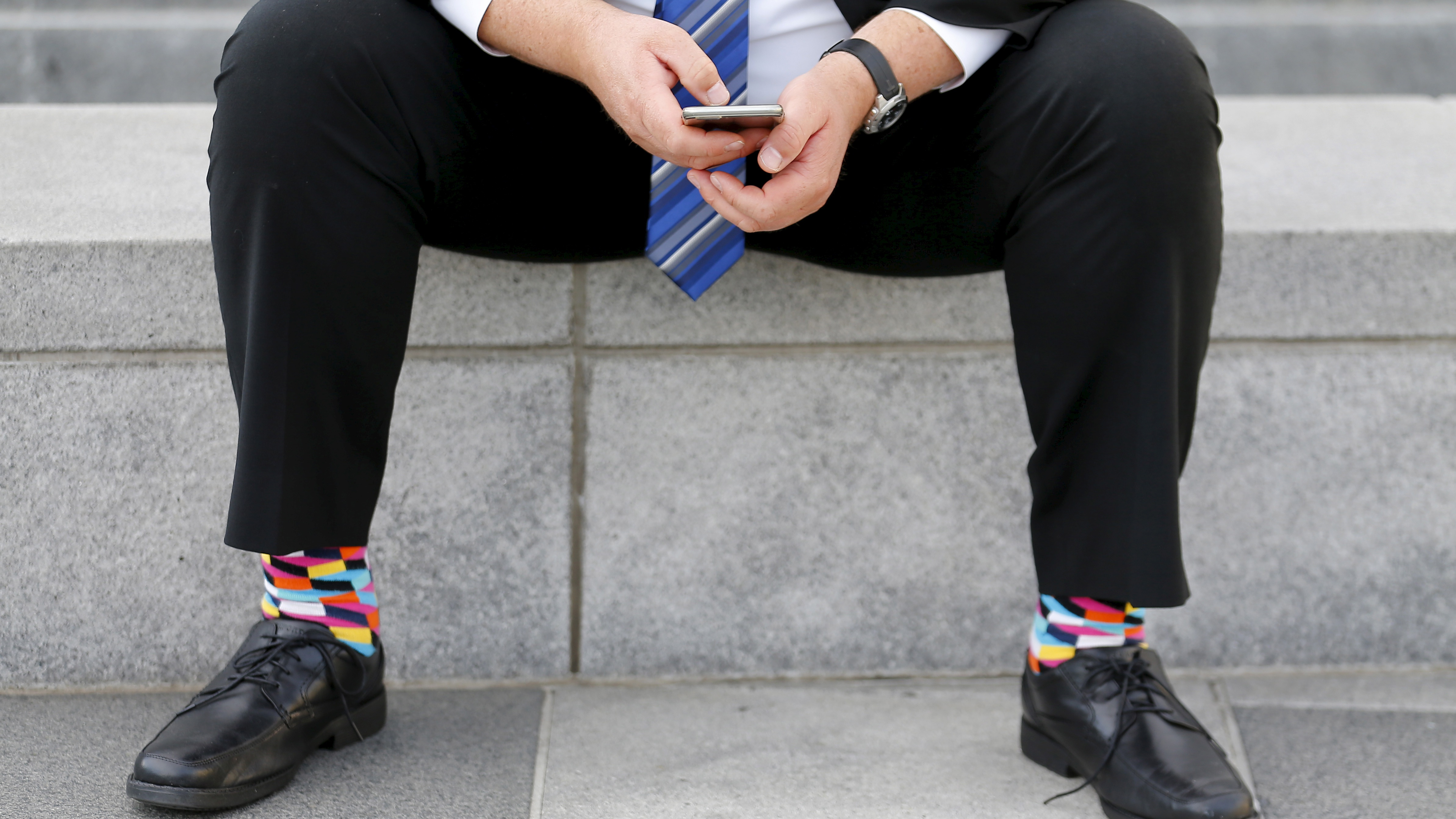 A businessman sits on a bench looking over his mobile phone in downtown San Francisco, California February 4, 2016.