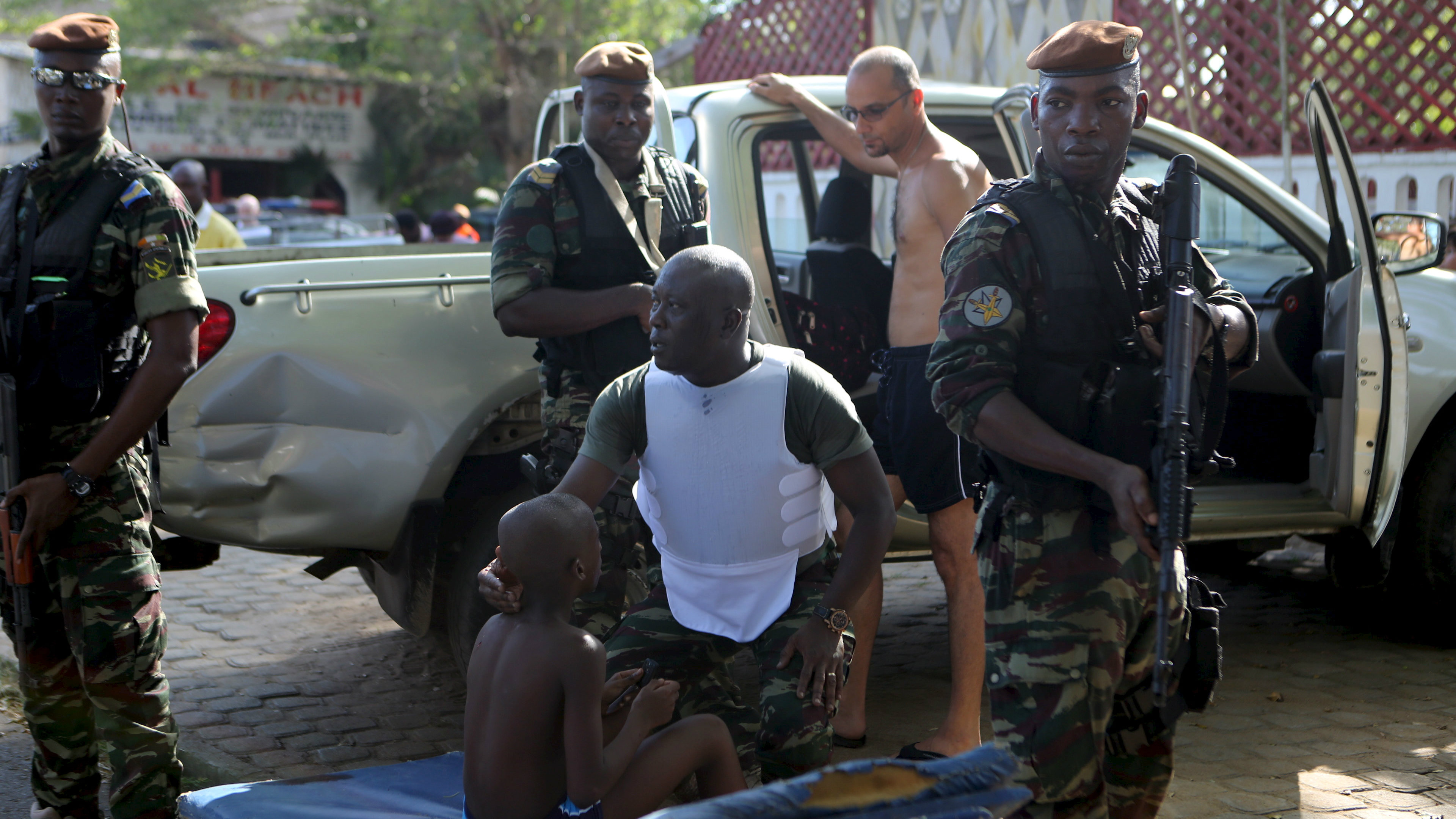 A soldier comforts an injured boy in Bassam, Ivory Coast, following an attack that left 18 people dead.