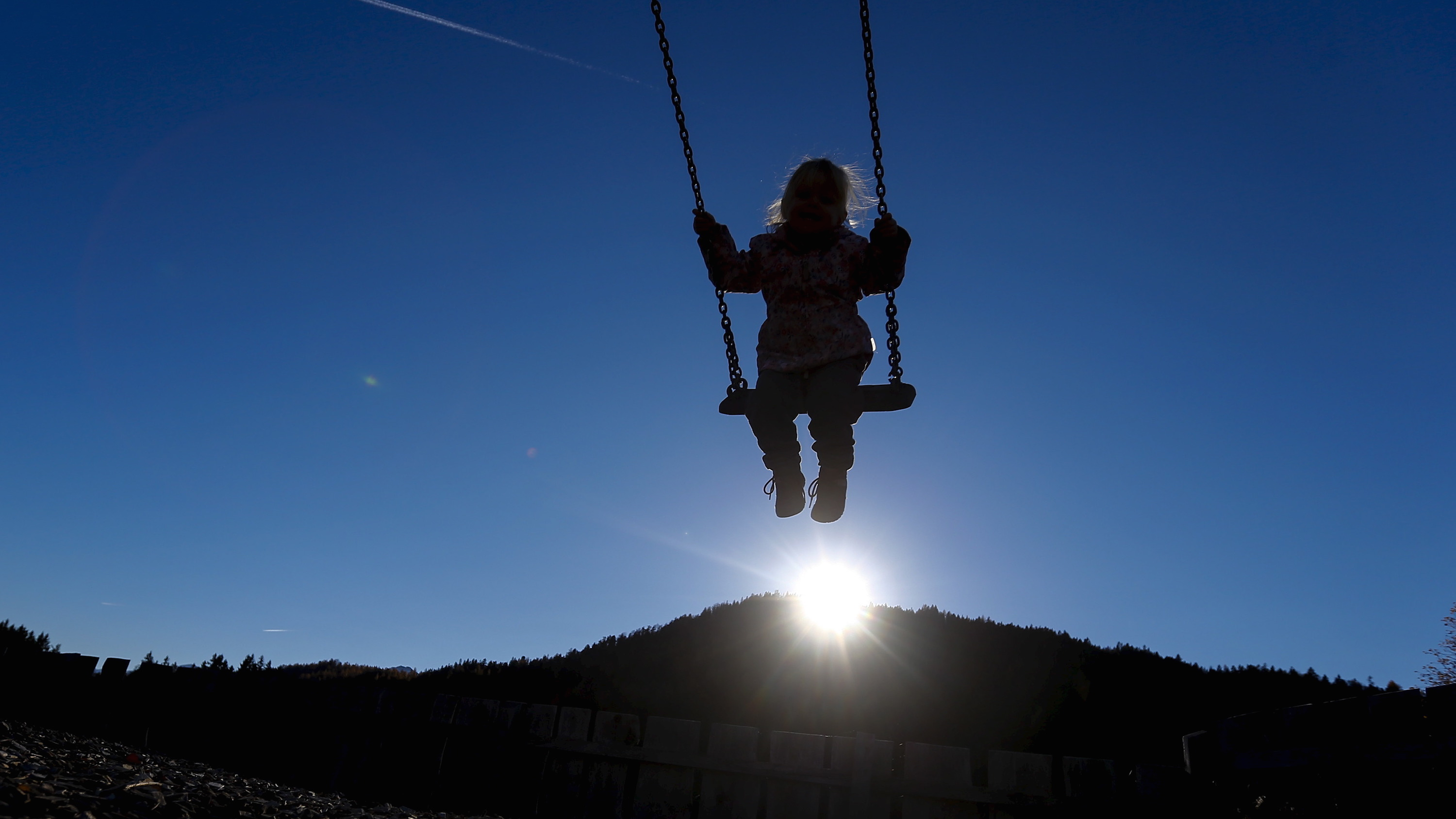 A silhouetted girl sits on a swing during a warm autumn day in the western Austrian village of Seefeld