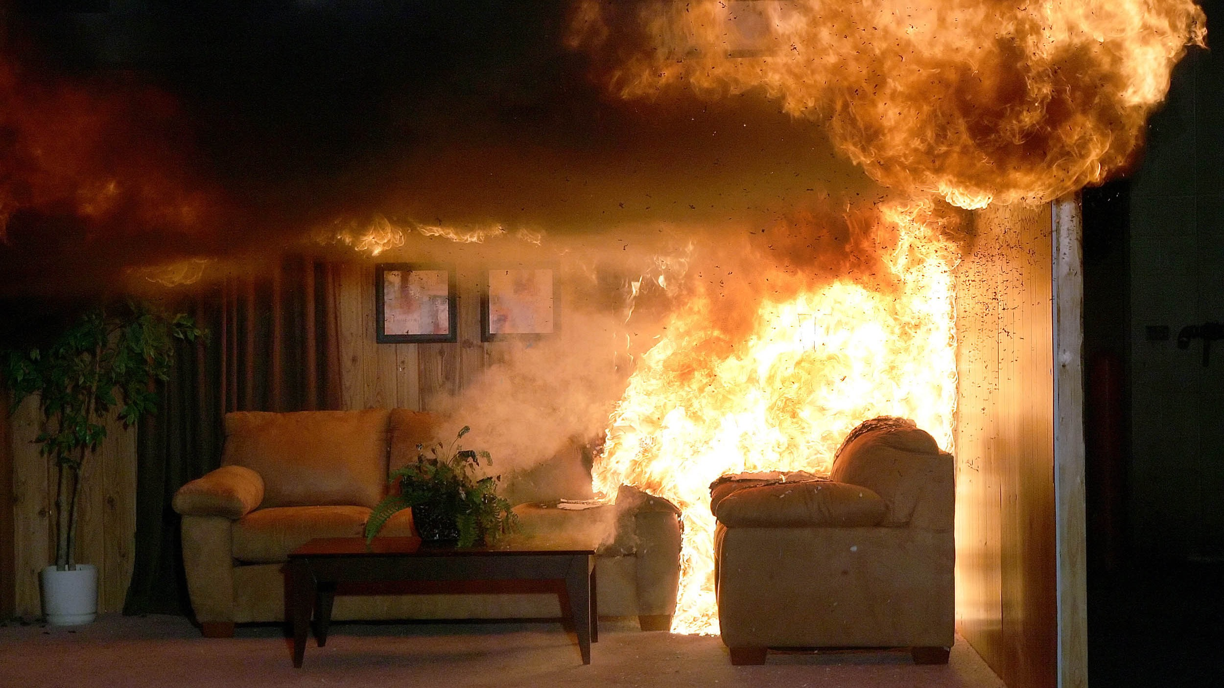 A living room, constructed by Underwriters Laboratory workers, is set on fire to test how fire-proof certain products are at the UL facility in Northbrook, Illinois August 24, 2006. REUTERS/Frank Polich (UNITED STATES) - RTR1IX76