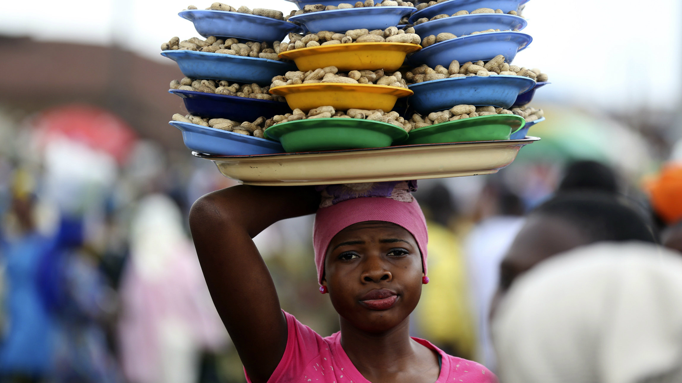 A girl hawks groundnuts arranged on a tray along a road in Nigeria's southwest city of Osogbo, August 11, 2014.