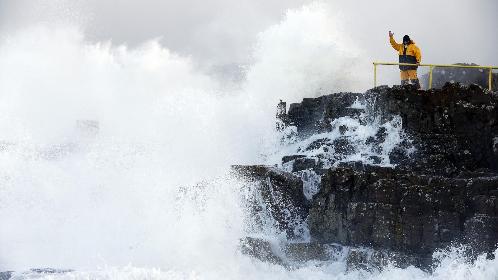 Man signals as waves crash