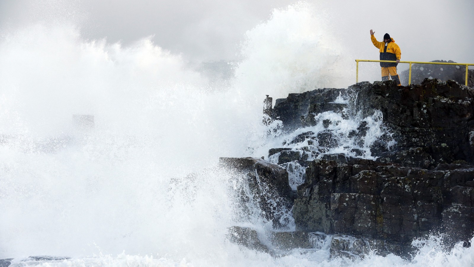 """A man signals as waves crash against the shore at Portstewart in northern Ireland December 10, 2014. Up to 17,000 residents in the west of Scotland were left without power on Wednesday morning as a """"weather bomb"""" of wet and windy conditions battered parts of Britain with gusts expected to reach up to 80 miles per hour (130 km/h). REUTERS/Cathal McNaughton (NORTHERN IRELAND - Tags: ENVIRONMENT) - RTR4HH4G"""