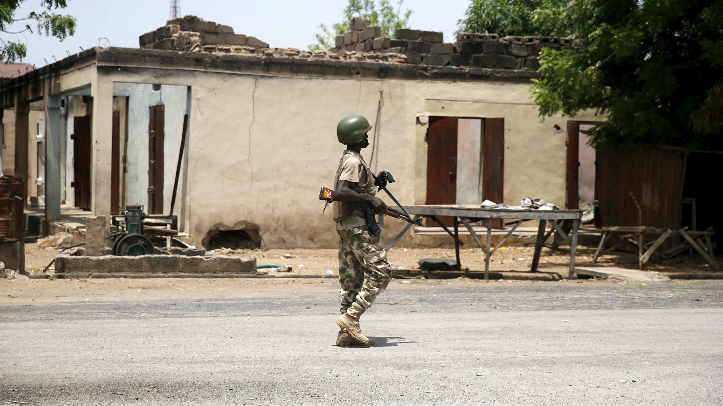 A soldier walks past a burnt building in Michika town, after the Nigerian military recaptured it from Boko Haram, in Adamawa state May 10, 2015.