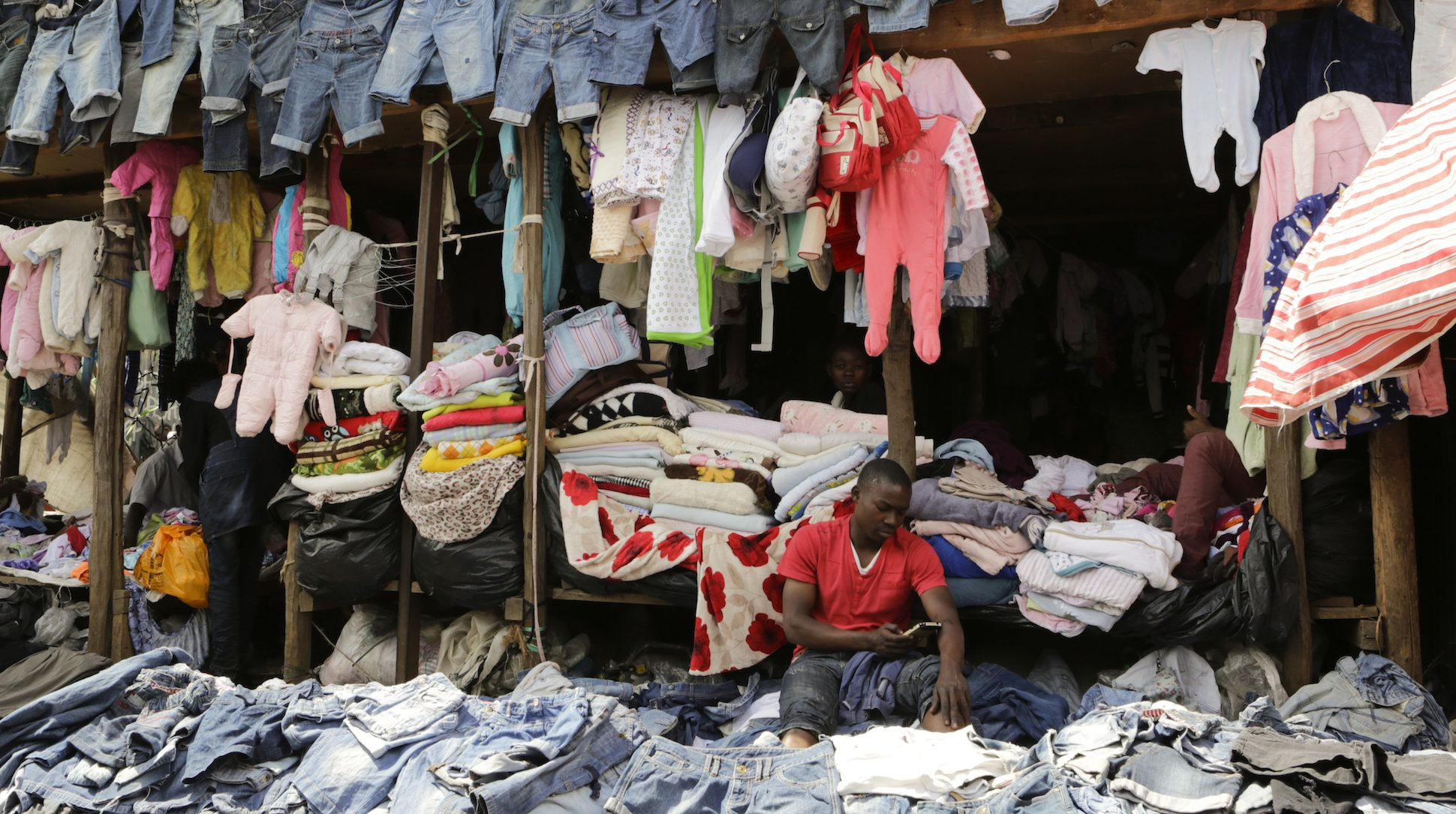 A trader (R) waits for customers at his stall selling secondhand clothes locally known as 'mitumba' at the Gikomba open-air market in Nairobi, Kenya, 27 July 2016. The Gikomba market in Nairobi is said to be the biggest second-hand clothes market in East Africa with close to 65,000 traders. The second-hand clothes sold in Gikomba are mostly imported from North America and Europe, according to a trader at the market. While 'mitumba' is considered to have brought down the market for locally made clothes and fabrics, it has also opened new opportunities for business people and new upcoming designers and stylists who rely on the second-hand clothes in their daily work as the second-hand clothes are considered to be easily available, affordable and provide a wide range of fashion styles, colors and fabrics compared to locally manufactured fashion apparels. Therefore they sell faster and in large quantities