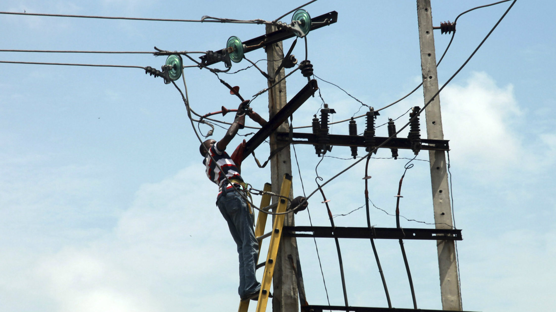 A power official works on an electric pole along a street in Nigeria's commercial capital Lagos October 3, 2012