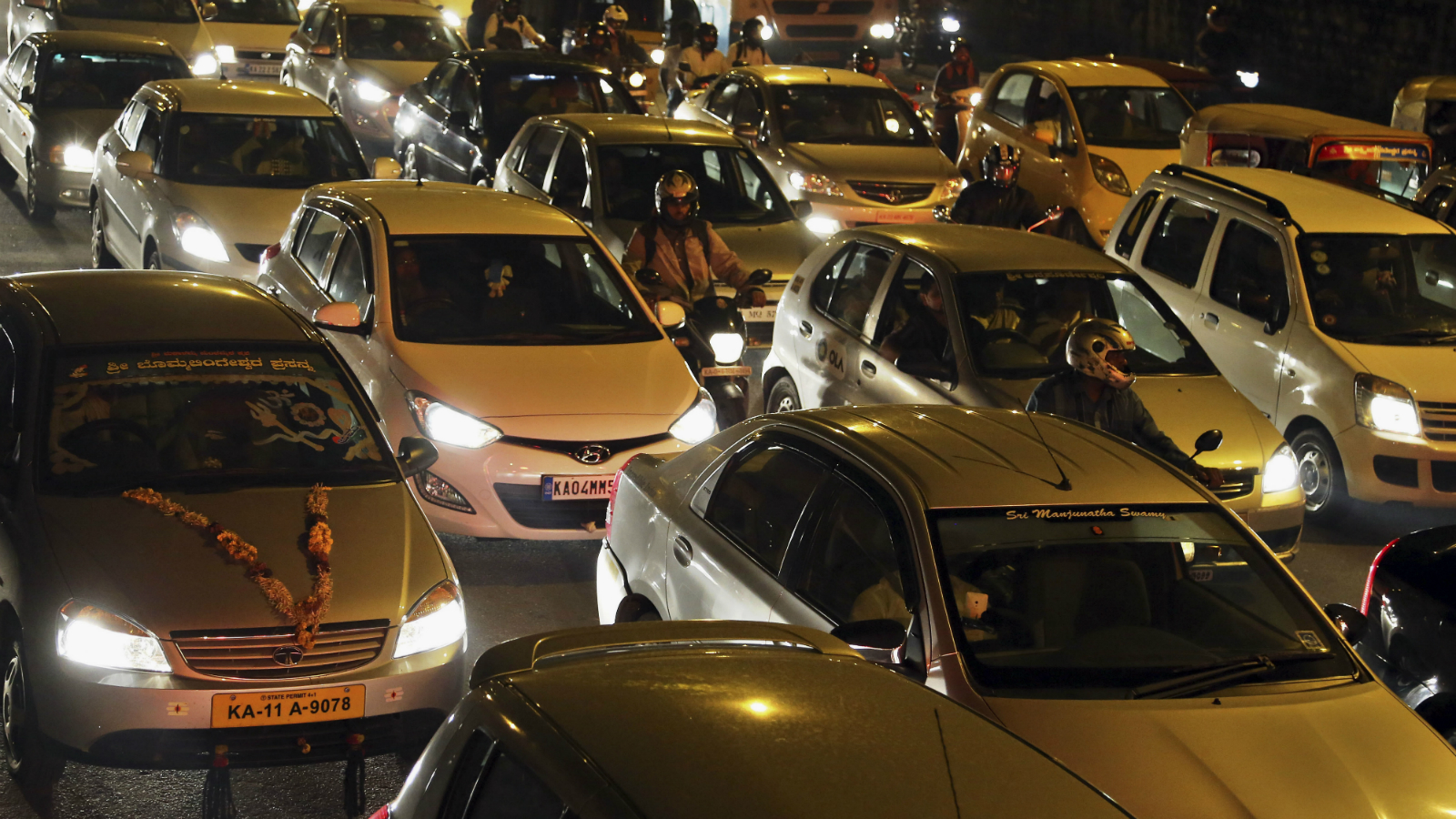 Traffic moves slowly during rush-hour in Bangalore, India, Tuesday, June 2, 2015. India's central bank cut a key interest rate by a quarter percentage point Tuesday, the third such reduction this year in support of government efforts to boost growth.