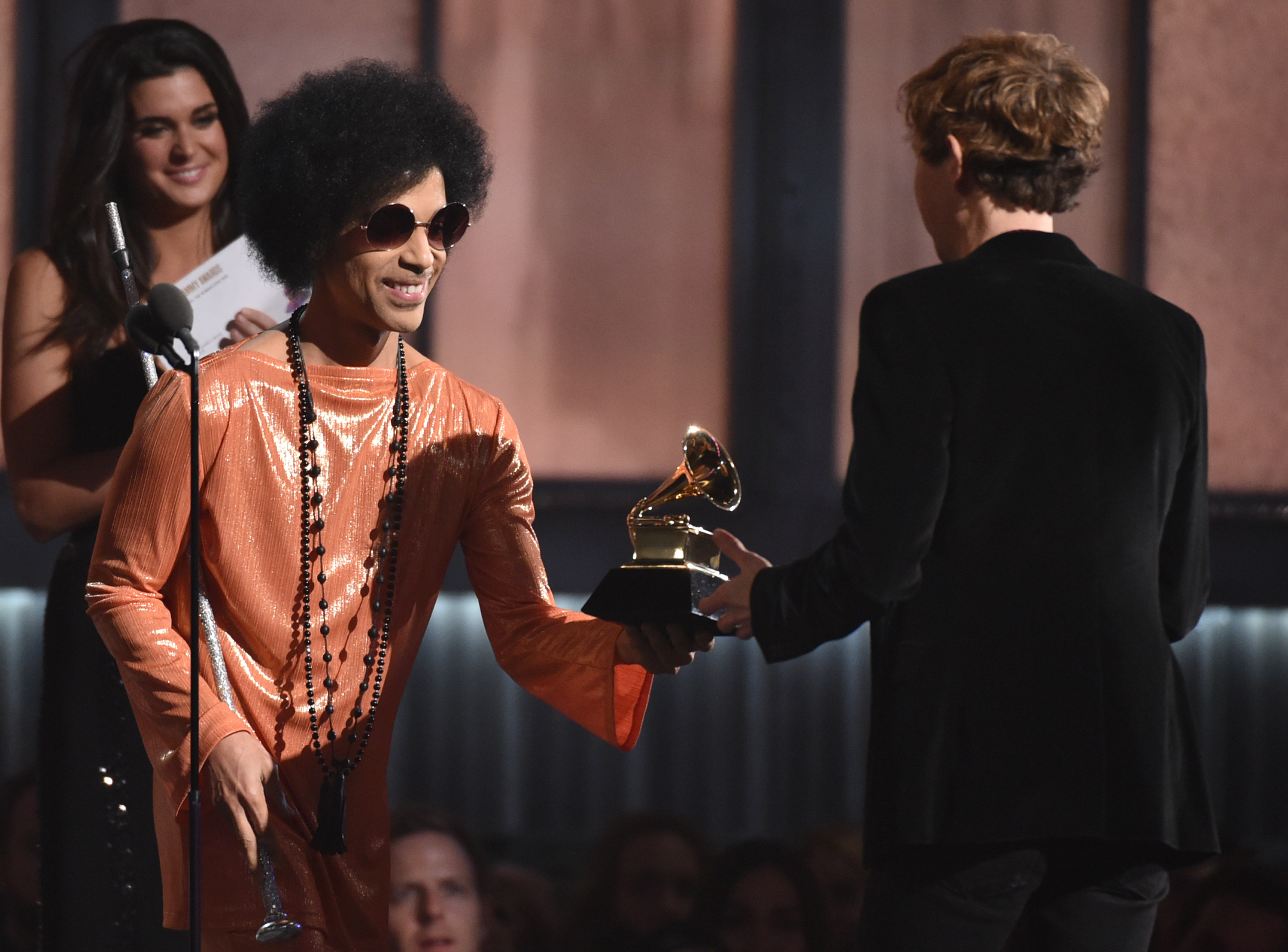 "Prince, left, presents Beck with the award for album of the year for ""Morning Phase""at the 57th annual Grammy Awards on Sunday, Feb. 8, 2015, in Los Angeles. (Photo by John Shearer/Invision/AP)"