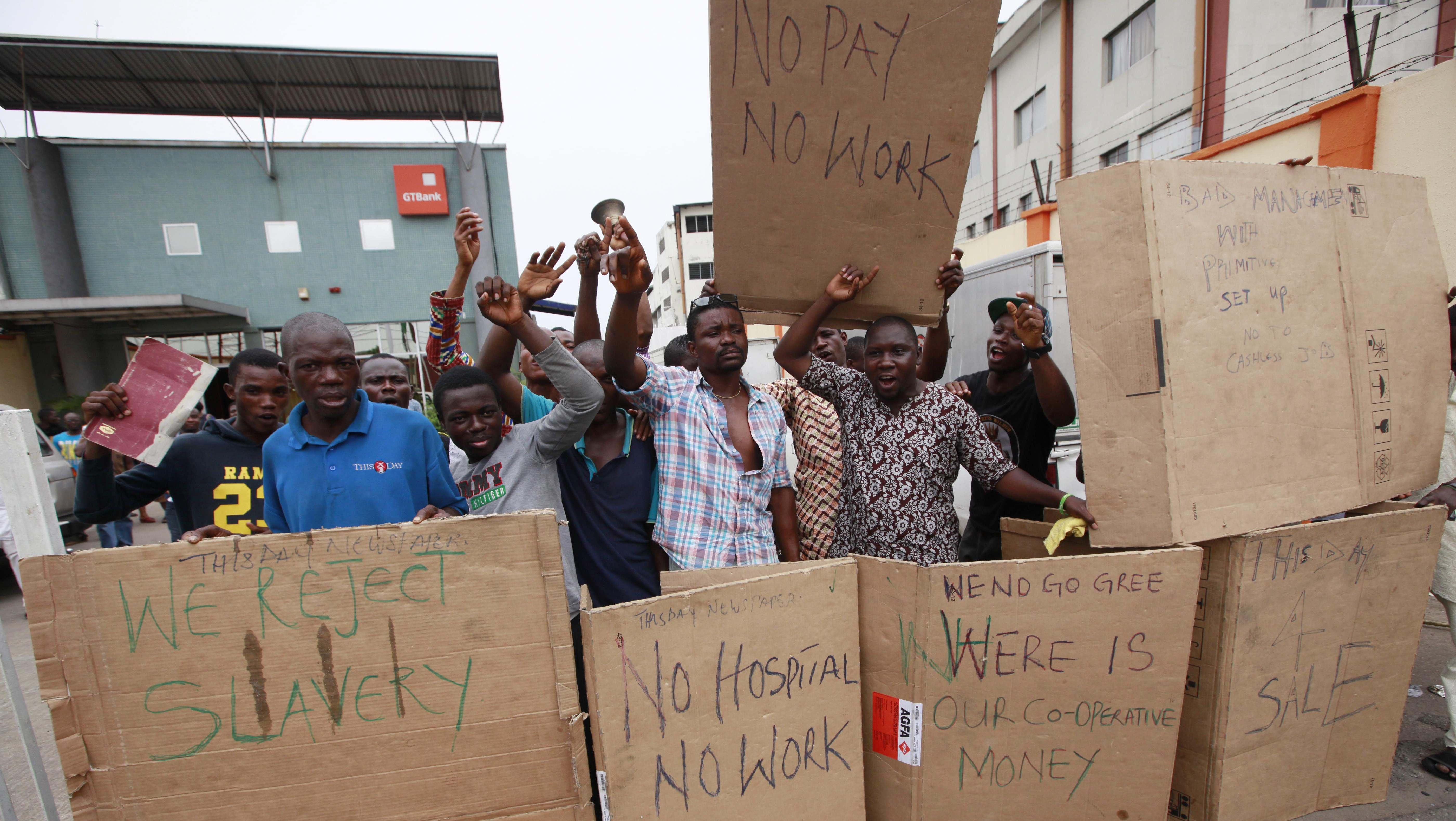Workers of This Day newspaper protest and barricade the front office due to non payment of salaries, in Lagos, Nigeria, Friday, May 10, 2013. Known more for bringing in celebrities and smiling in photographs next to former Western leaders, a flamboyant Nigerian newspaper publisher now faces a challenge from his most vocal critics _ his own employees. Workers have barricaded the front of This Day newspapers in Lagos, hoping to force publisher Nduka Obaigbena into paying them as much as four months' worth of back salaries due to them. Back pay disputes often hit industries in Nigeria, a country where steady paying jobs remain few, but this crisis has hit a man politically connected to the nation's ruling elite, the second such major business figure to be stung in recent months.(AP Photos/Sunday Alamba)