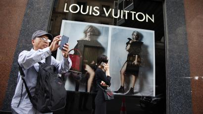 Chinese tourists take pictures outside the Galeries Lafayette general store in Paris, France