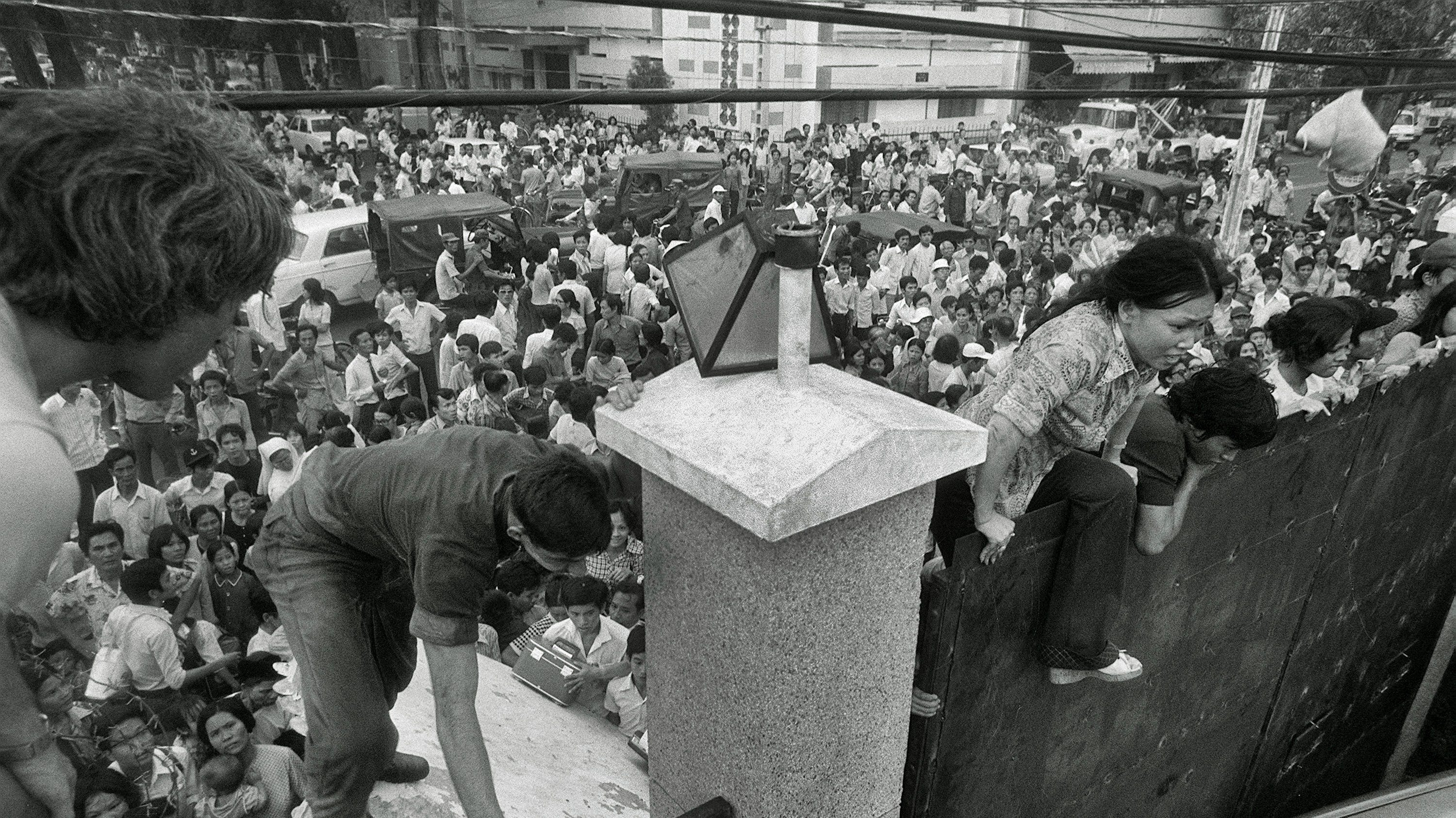 FILE - In this April 29, 1975 file photo, South Vietnamese civilians scale the 14-foot wall of the U.S. embassy in Saigon, trying to reach evacuation helicopters as the last Americans depart from Vietnam. (AP Photo/File)