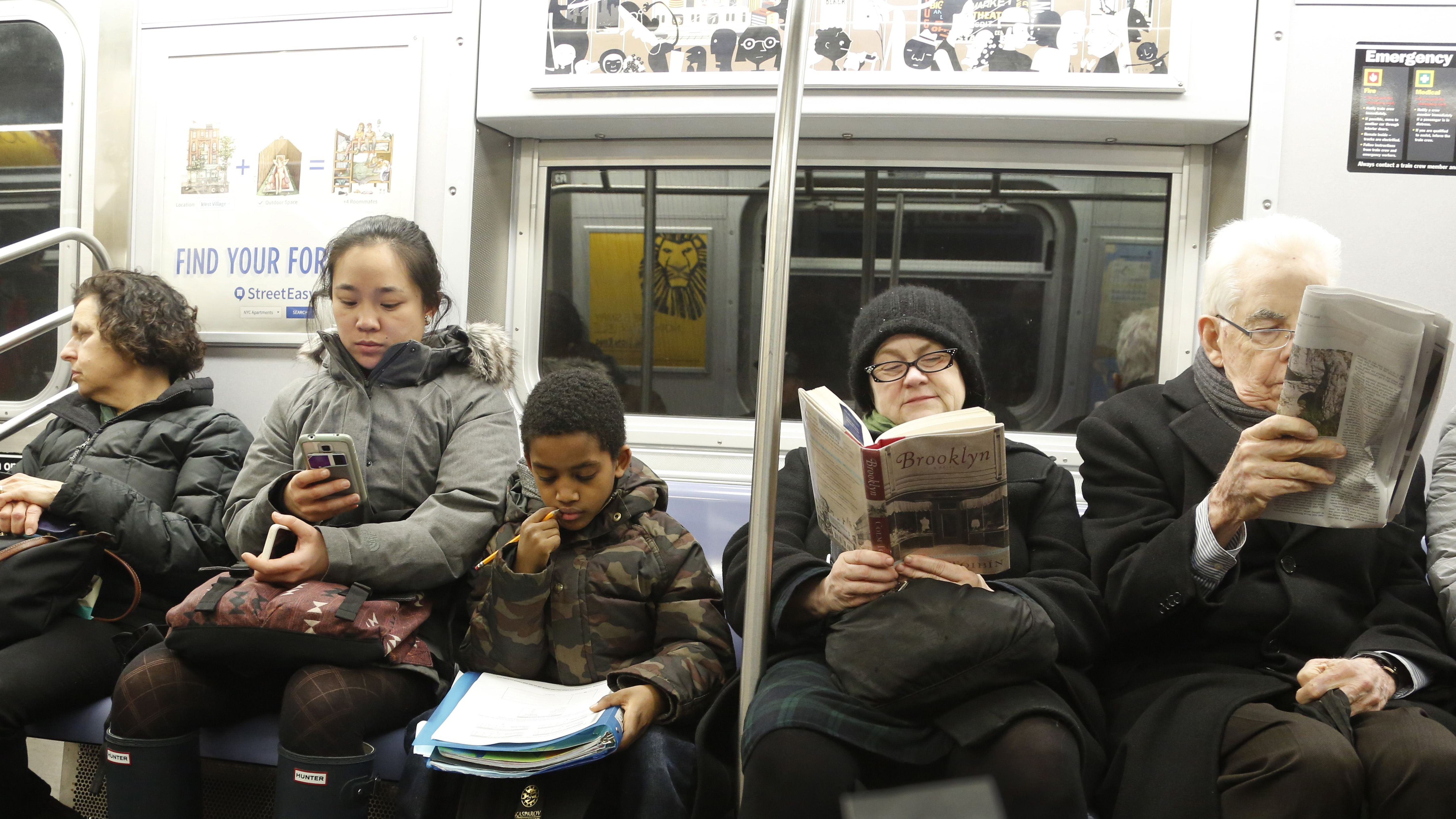 A schoolboy looks at his homework while riding the subway, Feb. 23, 2016 in New York. (AP Photo/Mark Lennihan)