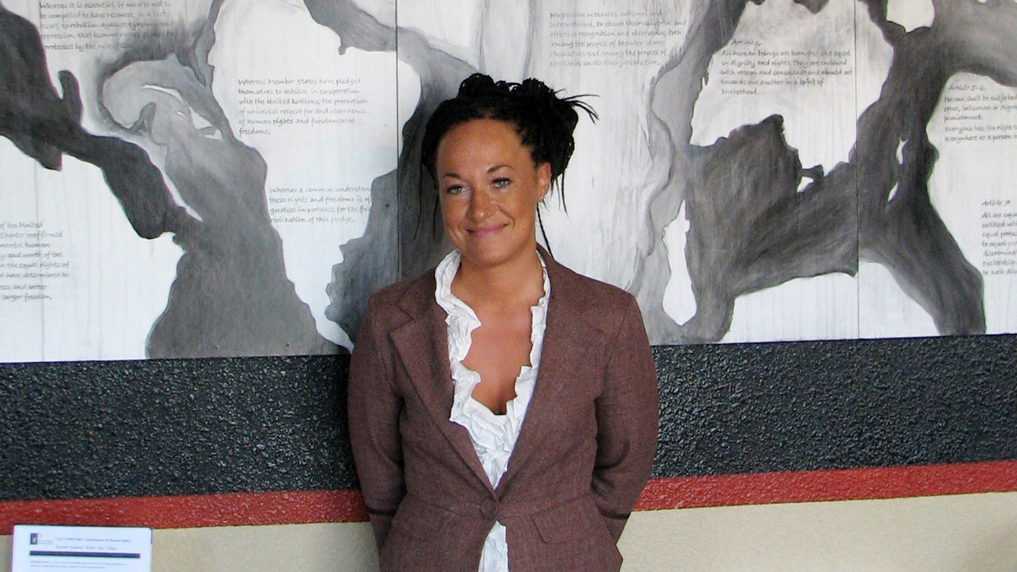 "FILE - In this July 24, 2009, file photo, Rachel Dolezal, a leader of the Human Rights Education Institute, stands in front of a mural she painted at the institute's offices in Coeur d'Alene, Idaho. Dolezal, the former NAACP chapter president who made headlines in June when her race came into question, faces that question Monday, Nov. 2, 2015, when she appears on the talk show ""The Real."" (AP Photo/Nicholas K. Geranios, File)"