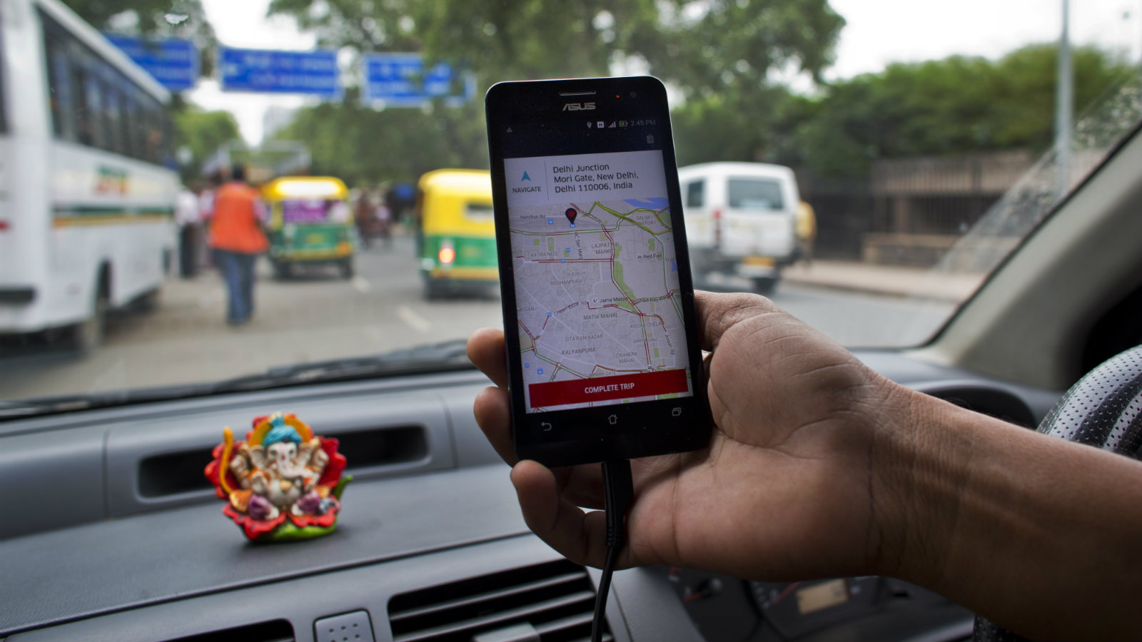 An Indian cab driver displays the city map on a smartphone provided by Uber as he drives in New Delhi, India, Friday, July 31, 2015. Ride-hailing service Uber has announced a $1 billion investment for the Indian market for the next nine months as it hopes to expand services and products, news reports said Friday.