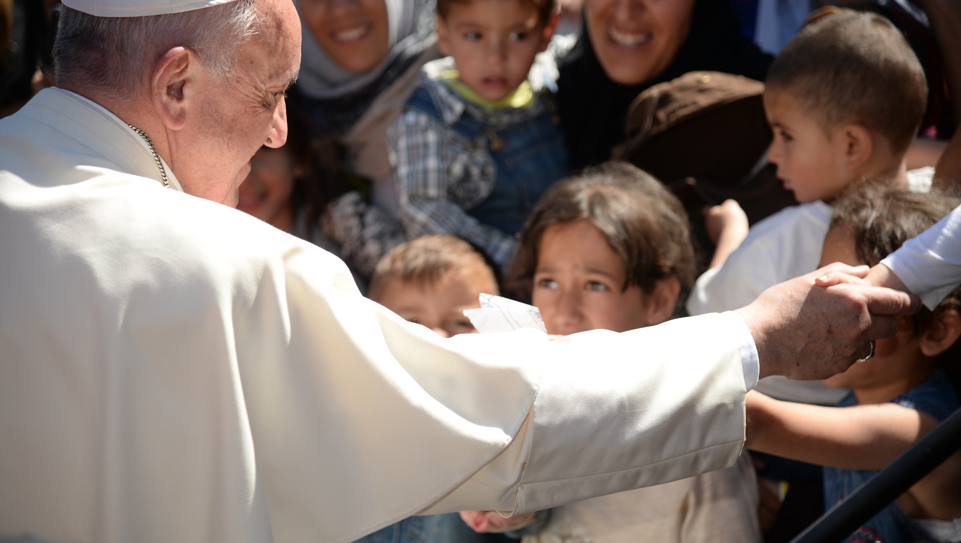 Pope Francis greets migrants and refugees at the Moria refugee camp on April 16, 2016 near the port of Mytilene, on the Greek island of Lesbos. Pope Francis received an emotional welcome today on the Greek island of Lesbos during a visit aimed at showing solidarity with migrants fleeing war and poverty.  Pope Francis, Orthodox Patriarch Bartholomew and Archbishop Jerome visit Lesbos today to turn the spotlight on Europe's controversial deal with Turkey to end an unprecedented refugee crisis.  AFP PHOTO POOL / FILIPPO MONTEFORTE