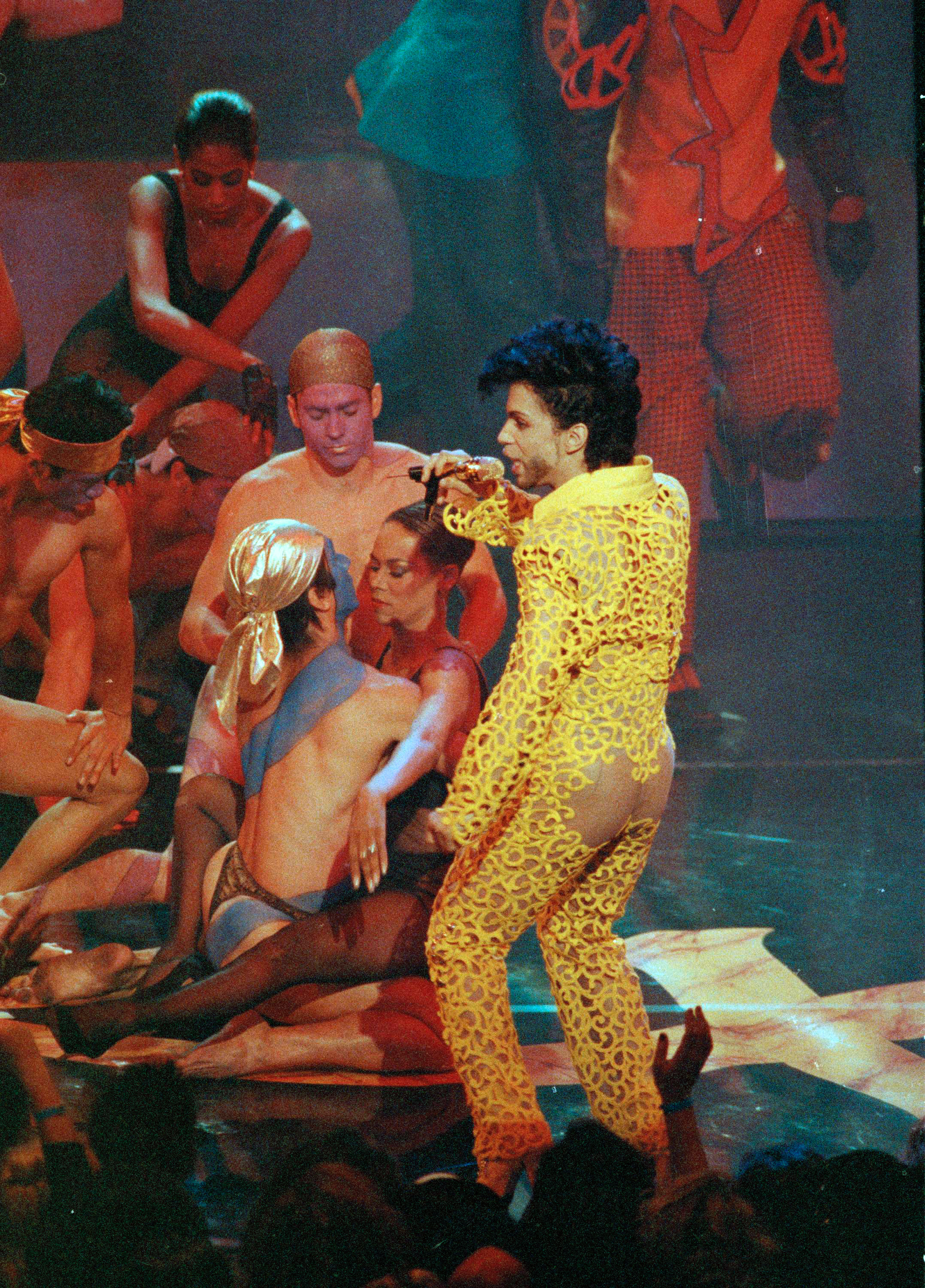 "EDITORS: PARTIAL NUDITY. Musician/singer Prince performs his single ""Get Off"", surrounded by half-naked dancers, while clad in a see through yellow suit at the 8th Annual MTV Video Music Awards in Universal City, Calif., Sept. 5, 1991. (AP Photo/Kevork Djansezian)"