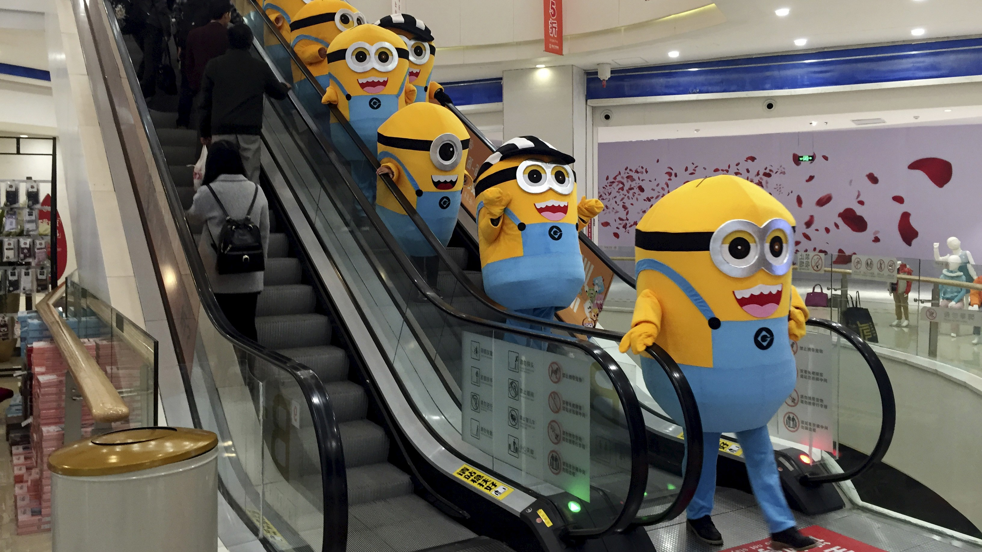 """People dressed as minions from the film """"Minions"""" take an escalator during a promotional event at a department store in Wuhan, Hubei province, China, November 14, 2015. Picture taken November 14, 2015."""