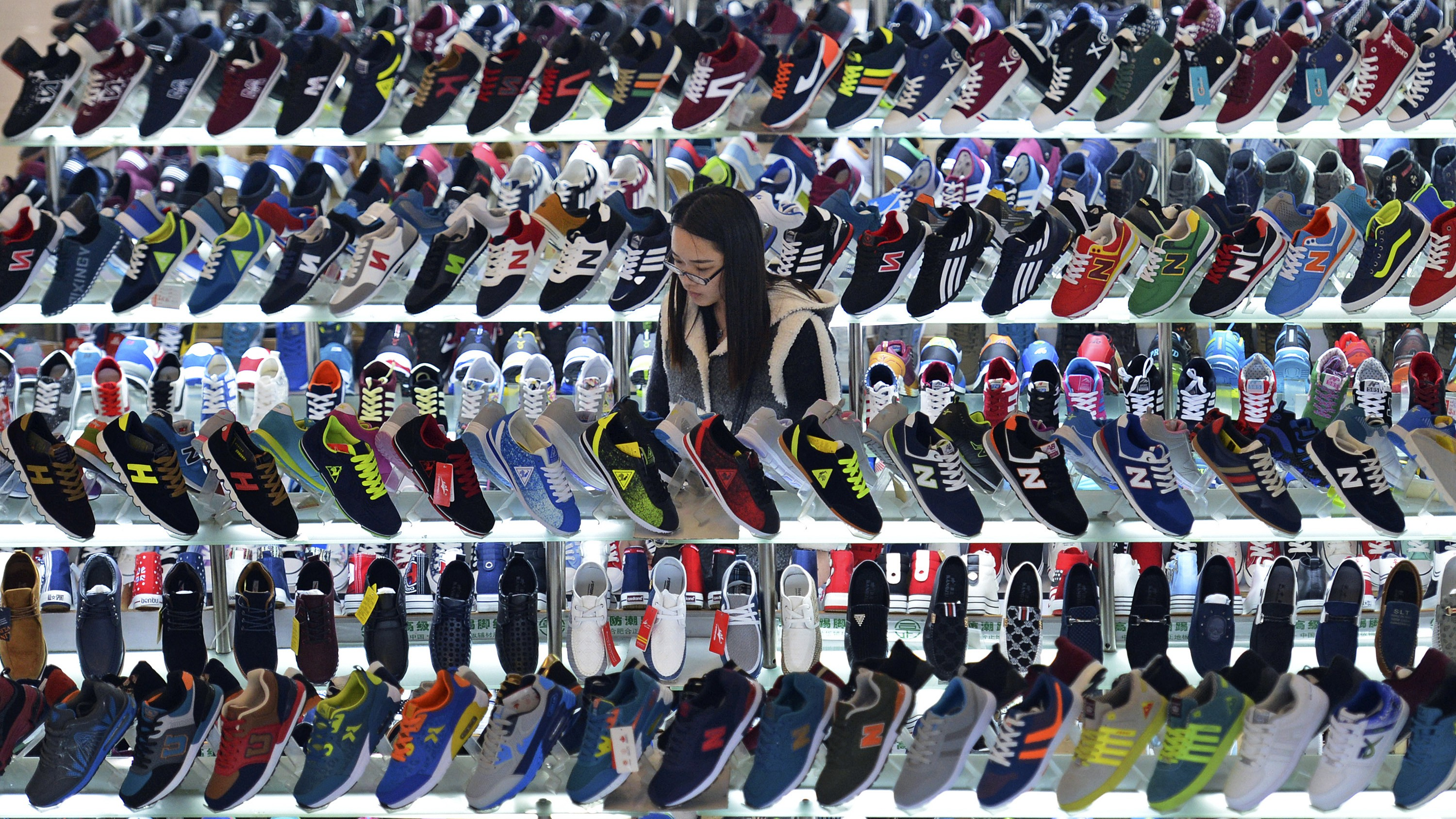 A customer shops for shoes at a mall in Hefei, Anhui province, March 10, 2015. China's annual consumer inflation recovered in February, exceeding expectations, but producer prices continued to slide, underscoring deepening weakness in the economy and intensifying pressure on policymakers to find new ways to support growth.