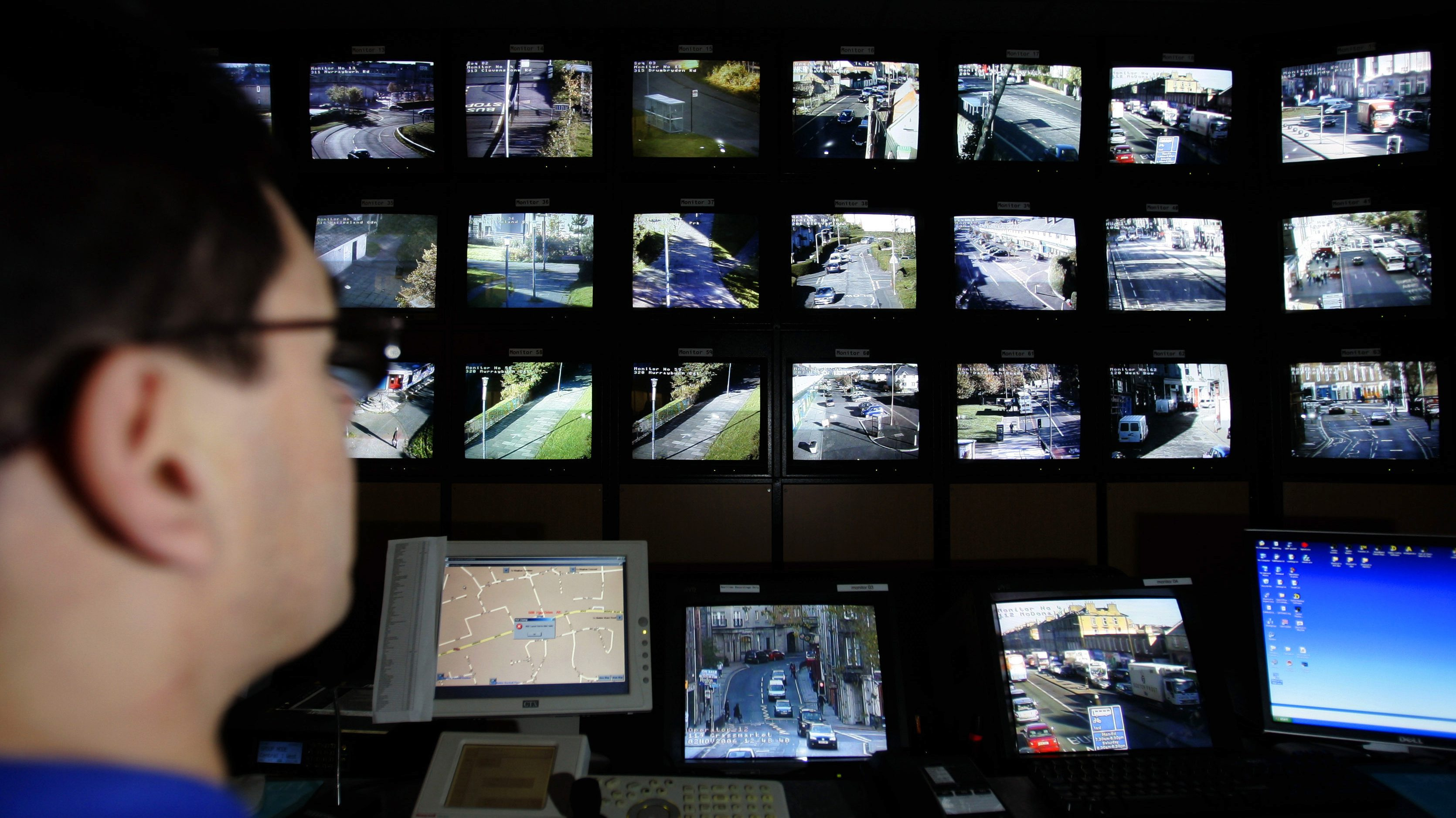 "A surveillance monitoring expert watches a bank of screens showing images from Edinburgh City Council's network of CCTV cameras in Edinburgh, Scotland November 2, 2006. Britain is becoming a surveillance society where individuals are filmed hundreds of times a day by security cameras and where firms ""data mine"" to build customer profiles, its information commissioner said on Thursday."