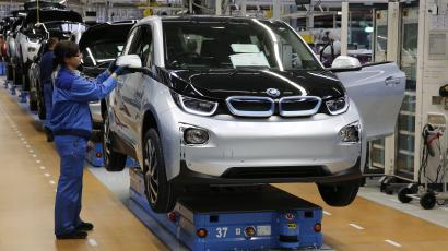 A worker makes final checks at the serial production BMW i3 electric car in the BMW factory in Leipzig