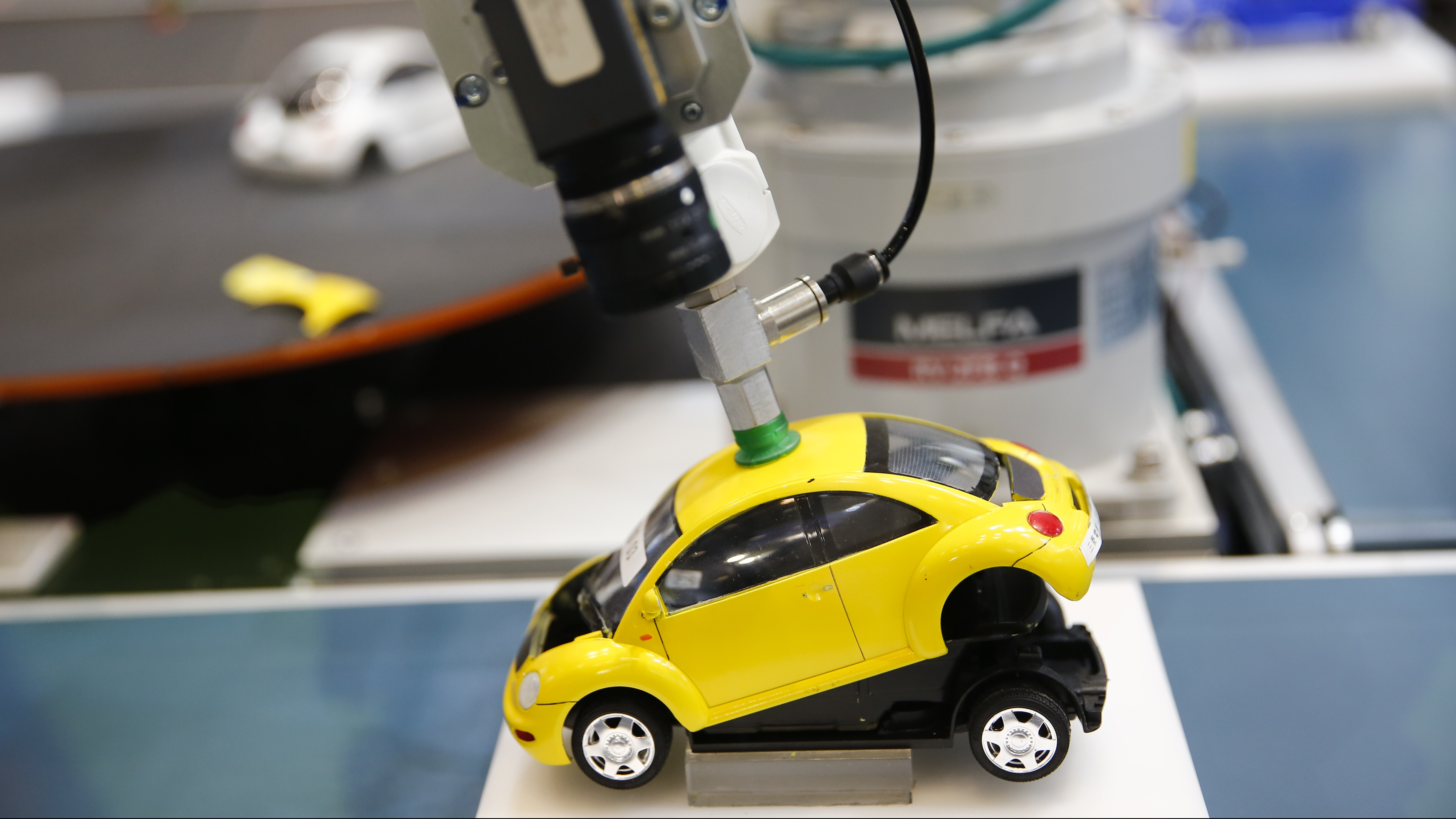 A robotic arm by Mitsubishi Electric assembles a toy car at the System Control Fair SCF 2015 in Tokyo