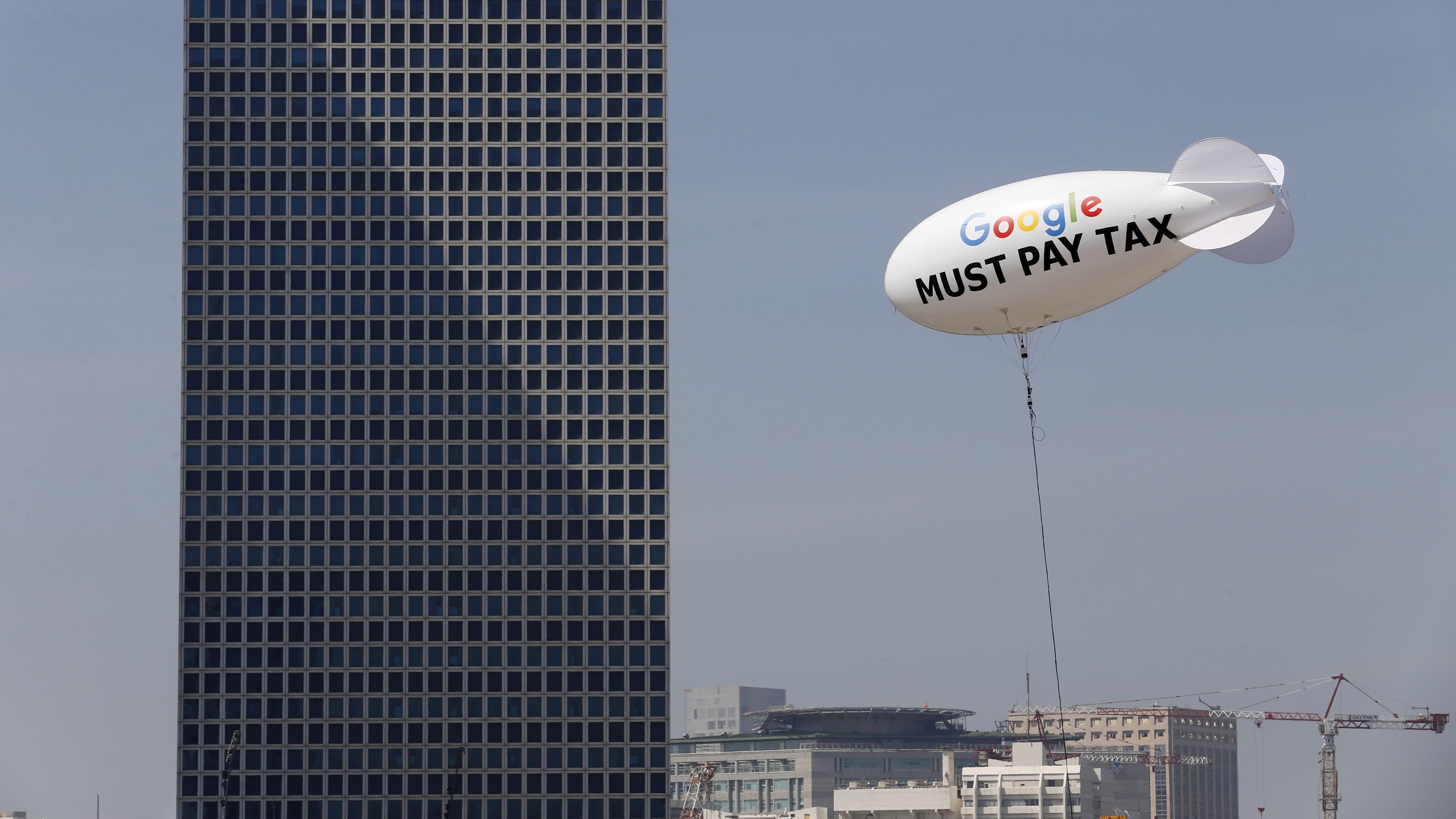 """A blimp reading """"Google must pay tax"""" is seen floating over the Tel Aviv skyline April 3, 2016. Israeli attorney Guy Ofir is the mastermind behind the blimp and told Reuters on Sunday that the airship will float until midnight some 200 meters from Google's offices with the intention of drawing public and media awareness to Google's tax issue."""