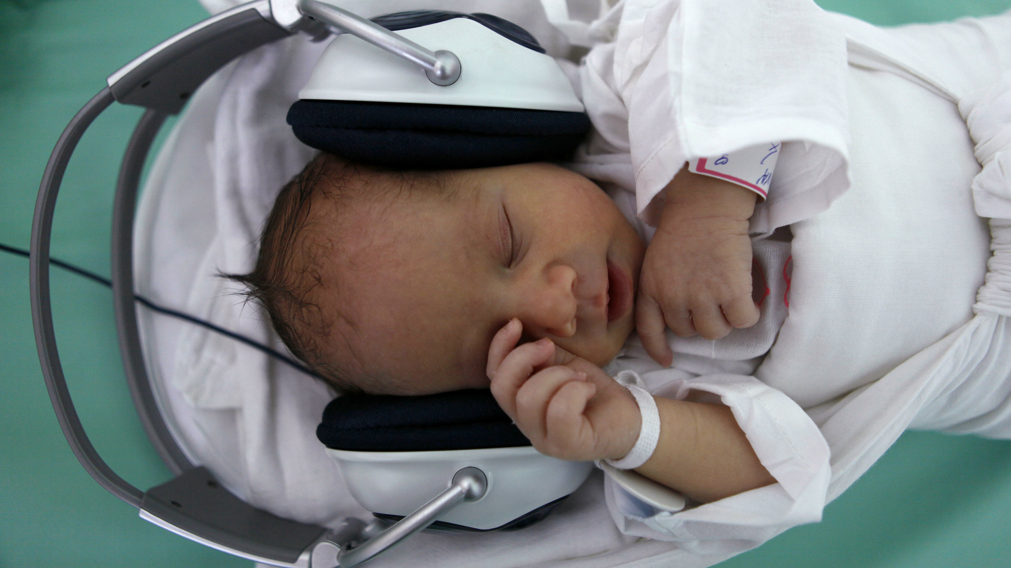 A newborn baby rests in a box, listening to music played through earphones in Saca Hospital in Kosice, east Slovakia May 25, 2011. The hospital uses music as therapy for newborn babies when they are separated from their mothers. REUTERS/Petr Josek (SLOVAKIA - Tags: HEALTH SOCIETY)