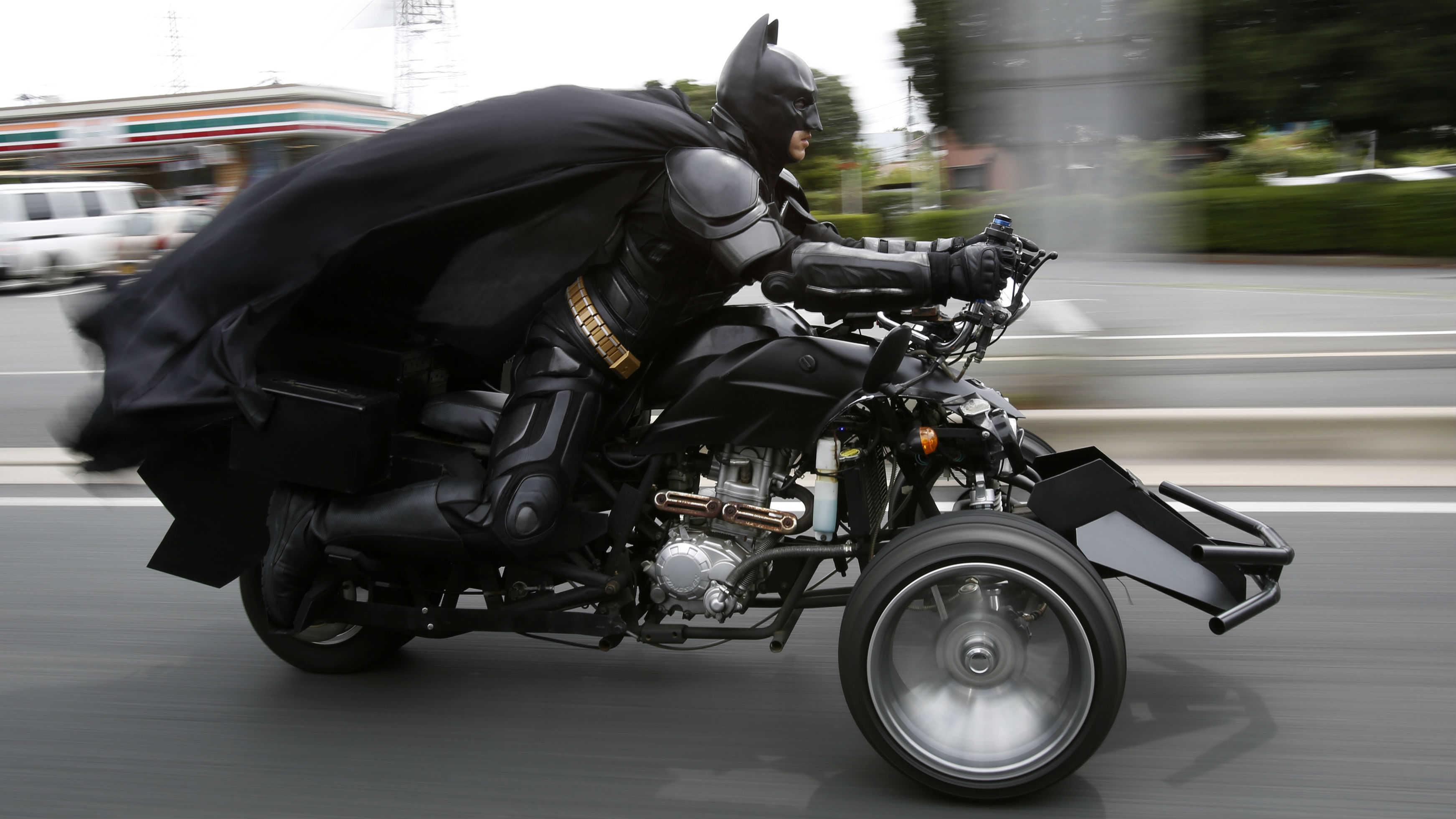 "A 41-year-old man going by the name of Chibatman rides his ""Chibatpod"" on the road in Chiba, east of Tokyo, August 31, 2014. The man, who dresses up as the comic book superhero Batman, came up with his moniker after adding a prefix of the first three letters of the city name, of which he roams on his three-wheeled motorcycle. However, unlike the hero from the Batman series, he rides around in his machine, designed from inspiration of the ""Batpod"" from the movies The Dark Knight and The Dark Knight Rises, delivering smiles instead of fighting crime."