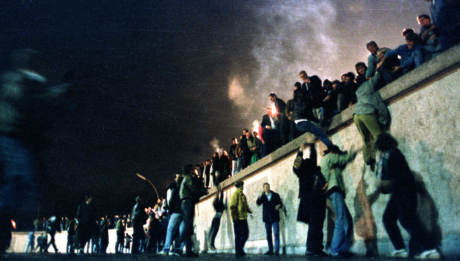 EAST GERMANS CLIMB THE BERLIN WALL IN THIS FILE PHOTO.