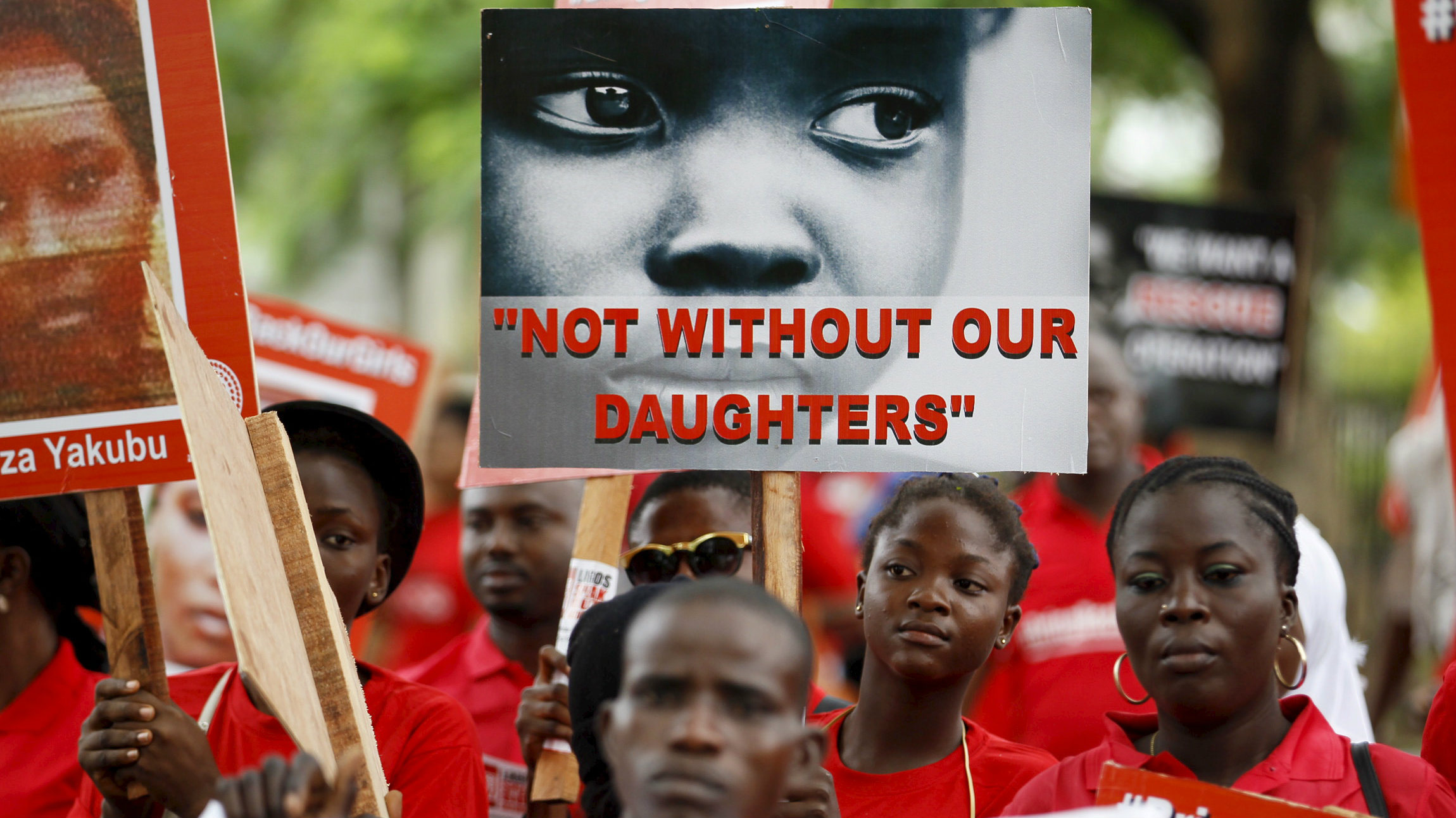Bring Back Our Girls (BBOG) campaigners hold banners as they walk during a protest procession marking the 500th day since the abduction of girls in Chibok, along a road in Lagos August 27, 2015.